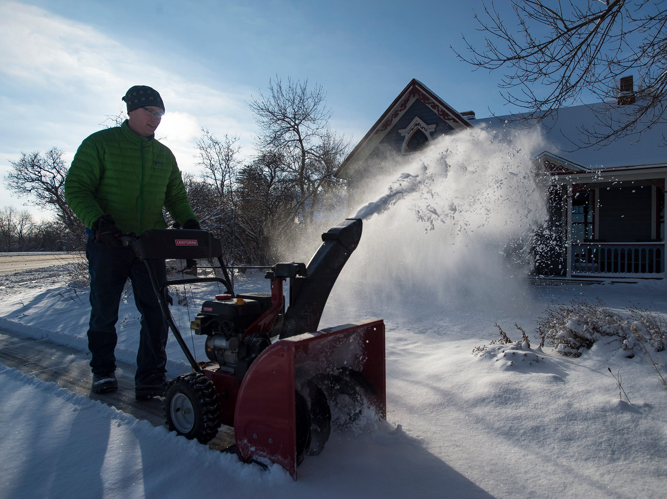 Fort Collins resident Sean Windsor runs his snowblower down his neighbor's sidewalk on Tuesday morning, Feb. 20, 2018, in Fort Collins, Colo.