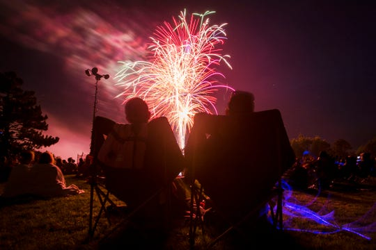 Martin Mendoza, left, and Jenrris Chavarria sit back and enjoy the fireworks on Wednesday night, July 4, 2018, at City Park in Fort Collins, Colo.
