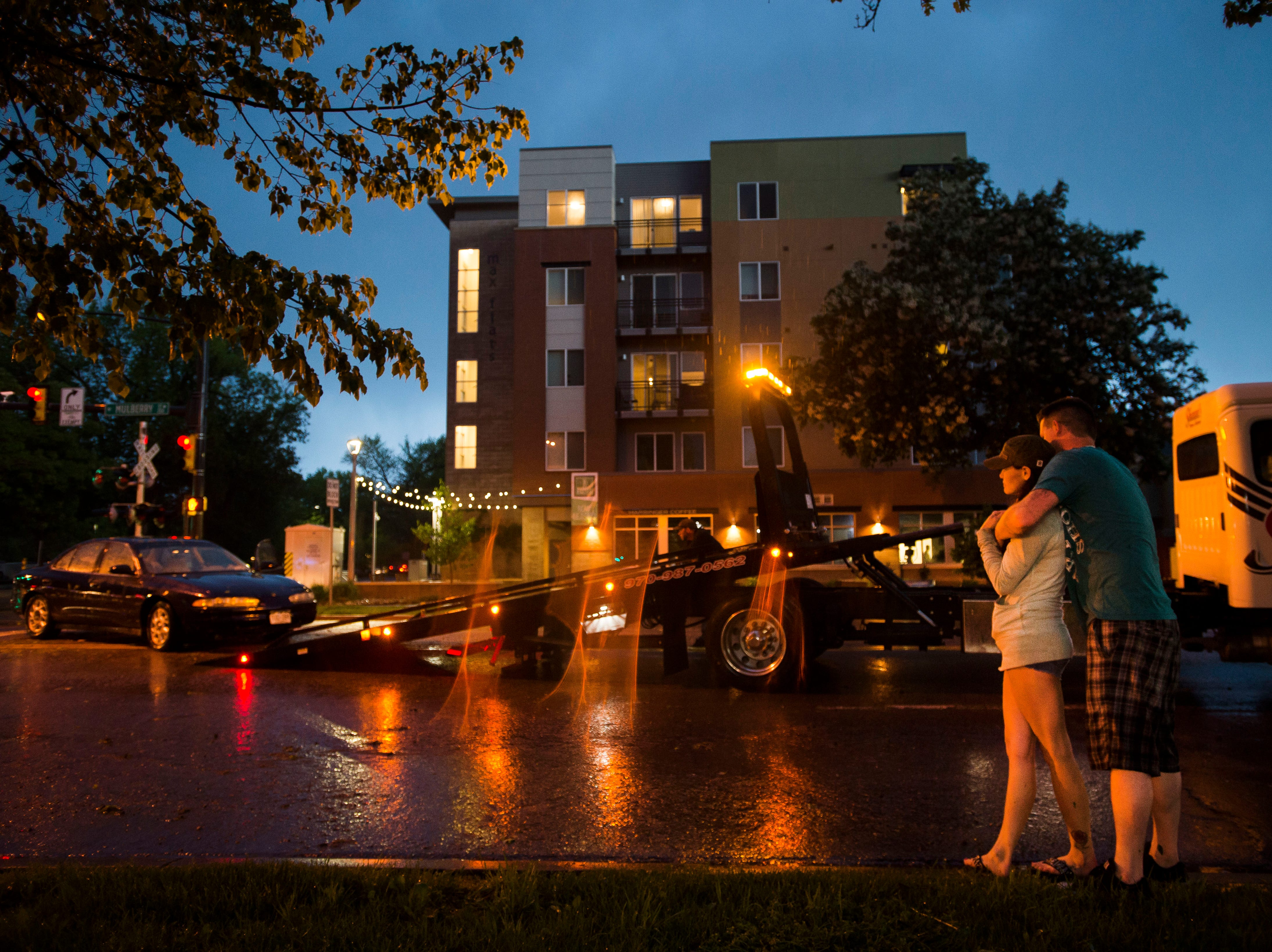 Katie Leech and her fiancŽ Mike Riley wait for he flooded car to be towed on Tuesday, May 22, 2018, at Mulberry and Mason Street in Fort Collins, Colo. Leech had to evacuate her car with her two young children when it was flooded out at the intersection and were taken in by Schrader gas station employee Shawn Dhariwal, who gave them towels and shelter immediately after.