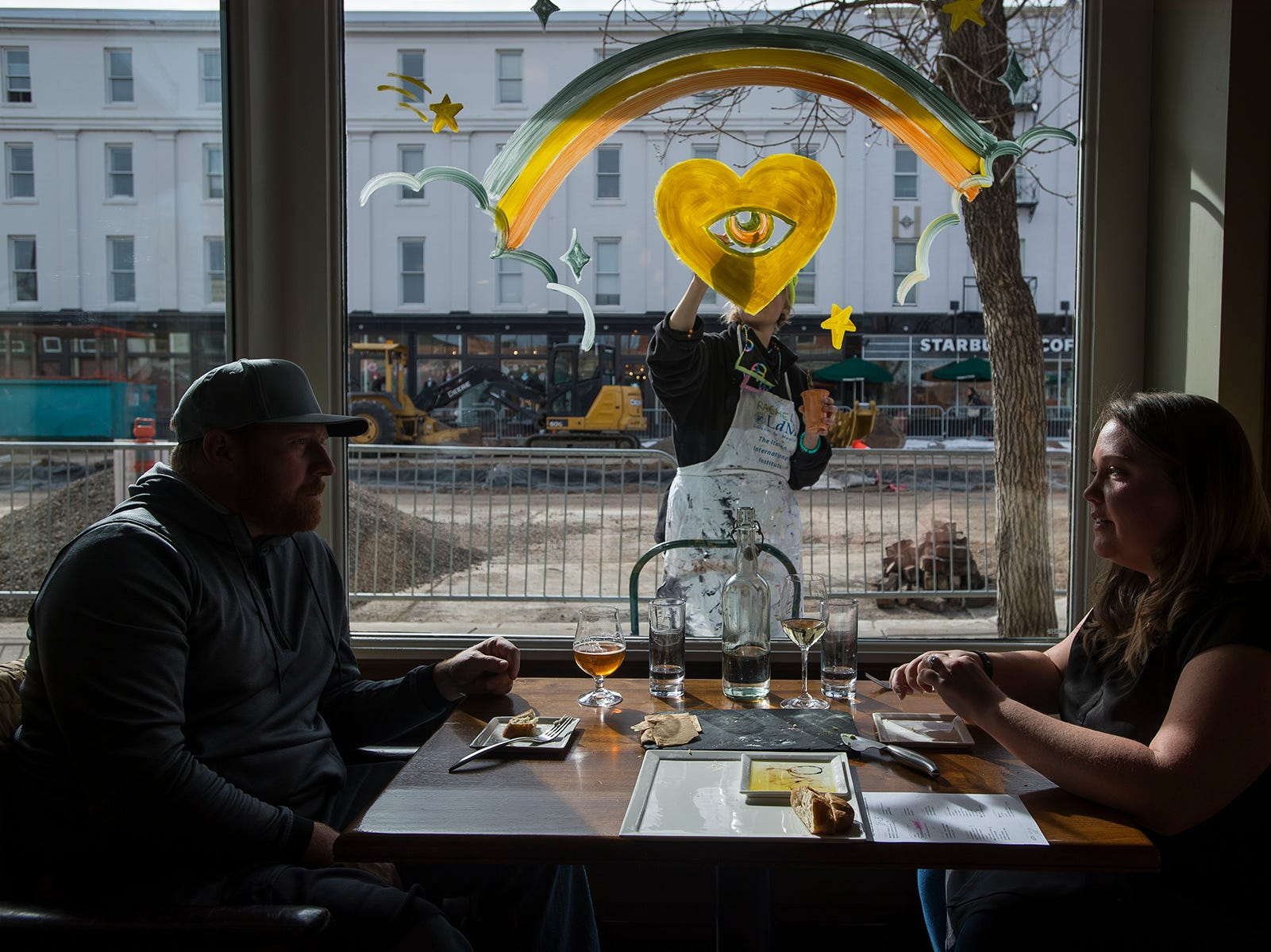 "Fort Collins residents Brandie and Tyler Bolton enjoy their lunch while local artist Rachel Becker, who works under the name ""Church of Earth,"" begins painting a mural of the front window of The Welsh Rabbit Cheese Bistro on Saturday morning, Jan. 27, 2017, on Walnut Street in Old Town Fort Collins, Colo."
