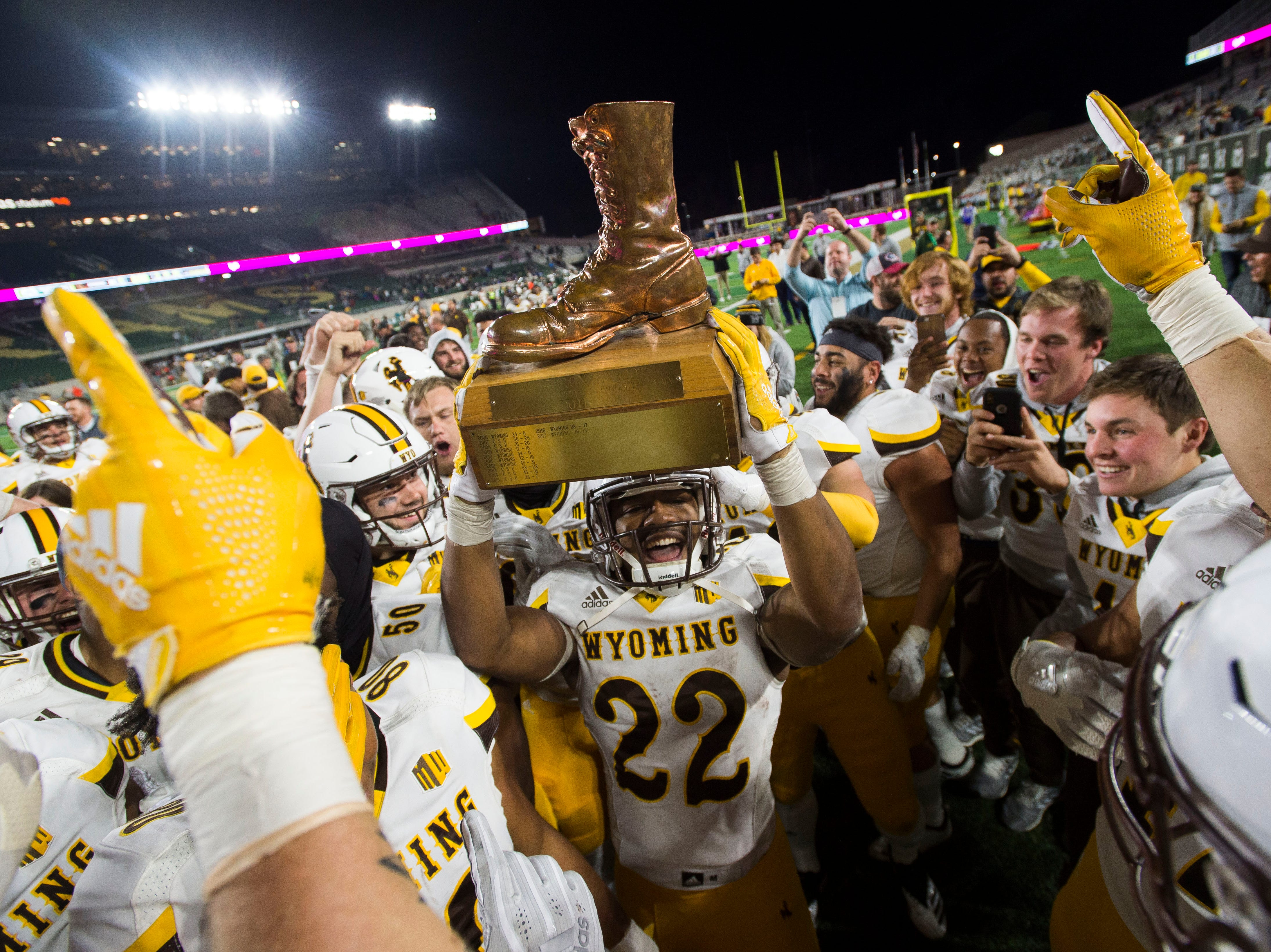 University of Wyoming senior running back Nico Evans (22) hoists up the bronze boot trophy after beating rival Colorado State University of on Friday, Oct. 26, 2018, at Canvas Stadium in Fort Collins, Colo.