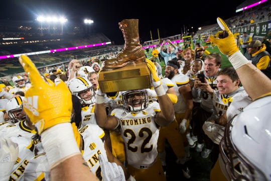 Wyoming running back Nico Evans (22) and his teammates celebrate with the Bronze Boot after defeating Colorado State's football team last season in Fort Collins to claim the traveling trophy in the annual Border War rivalry for the fourth straight year. The Bronze Boot will be at stake again Friday night, when the teams meet at War Memorial Stadium in Laramie, Wyo.