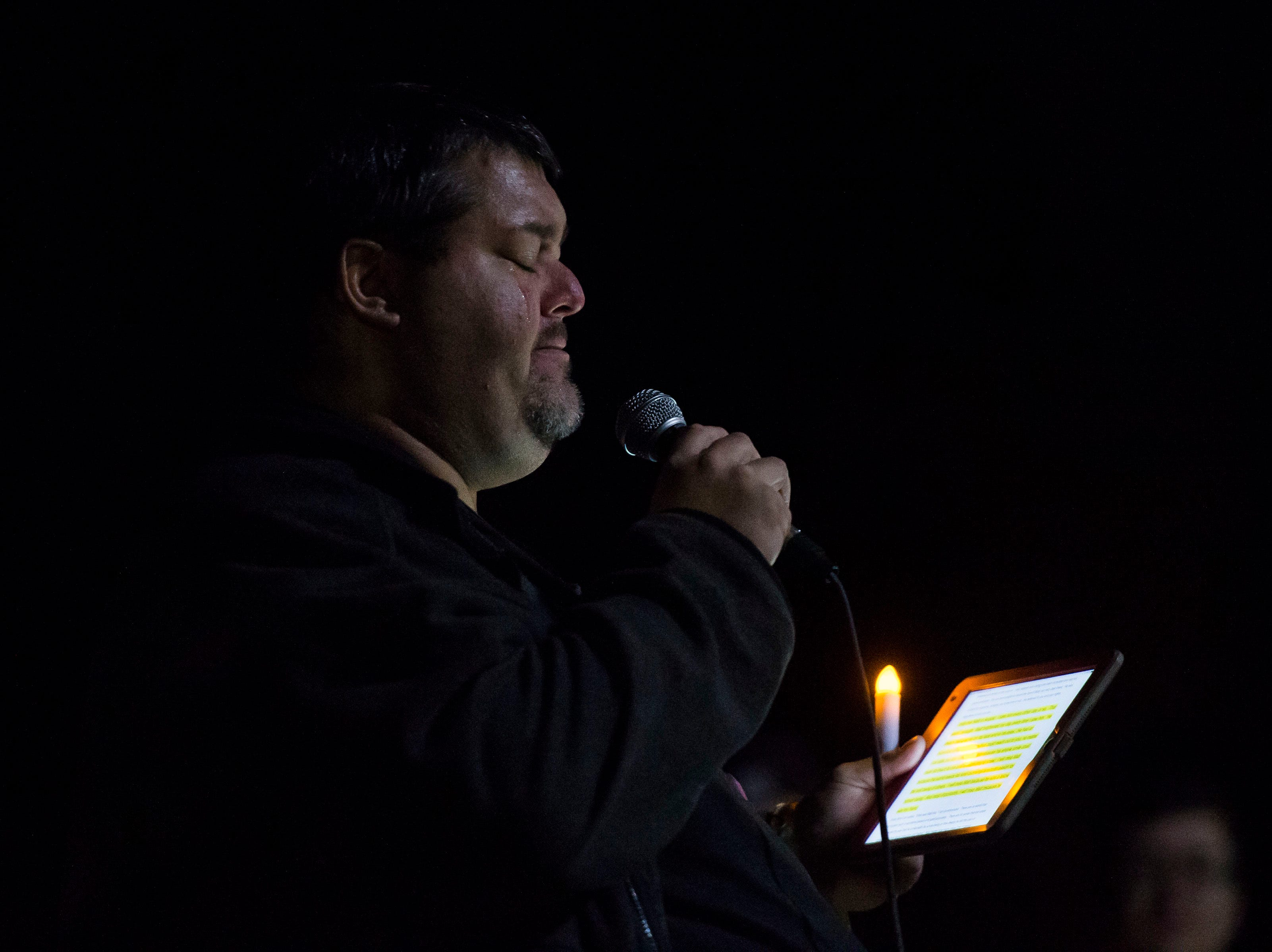 Tears run down Jim Osborn's face as he reads a speech during a candlelight vigil on the 20th anniversary of Matthew Shepard's death on Friday, Oct. 12, 2018, at Prexy's Pasture on the University of Wyoming campus in Laramie, Wyo.