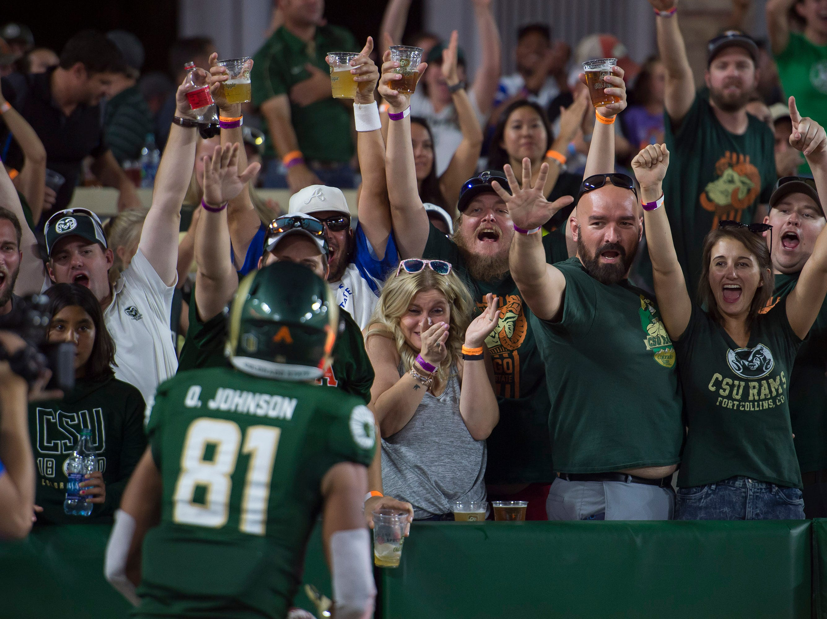 Fans on the New Belgium porch celebrate as Colorado State senior wide receiver Olabisi Johnson (81) scores a touchdown on a long reception from quarterback K.J. Carta-Samuels (1) during a game against the University of Hawaii Rainbow Warriors on Saturday, Aug. 25, 2018, at Canvas Stadium in Fort Collins, Colo.