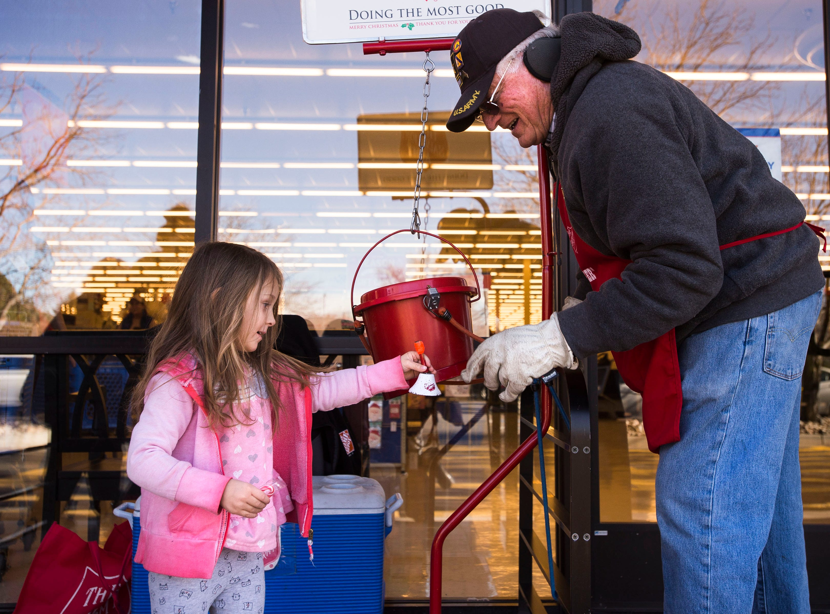 Salvation Army bell ringer is Robert Thompson lets three-year-old Emerson Fry ring the bell after dropping a donation into the bucket on Friday, Dec. 21, 2018, in front of the Hobby Lobby on South College Avenue in Fort Collins, Colo.