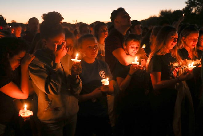 Mourners of those slain and injured in the Marjory Stoneman Douglas High School mass shooting attend a candlelight vigil at the Parkland Amphitheater on Thursday 2/15/2018. 17 people were killed in the shooting.