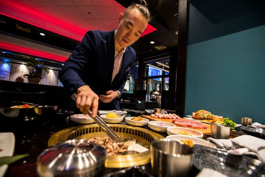 Chris Shin, Ember's general manager, shows how to cook on the in-table Korean barbecue grills. Ember Korean Steakhouse opened in mid-December in south Fort Myers.