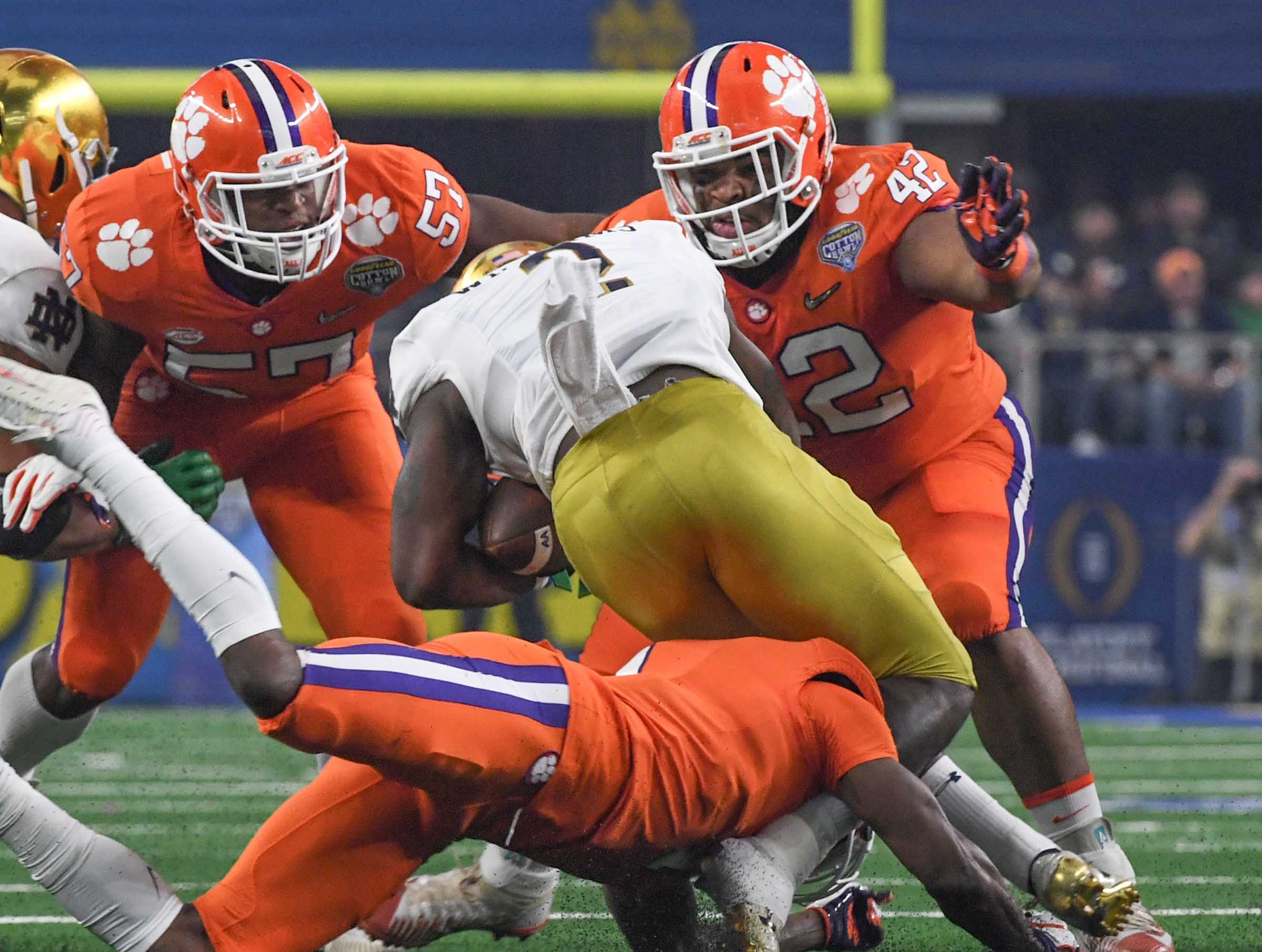 Clemson linebacker Tre Lamar (57), left, and defensive lineman Christian Wilkins (42) tackle Notre Dame running back Dexter Williams (2) during the College Football Playoff Semifinal at the Goodyear Cotton Bowl Classic at AT&T Stadium in Arlington, Texas Saturday.