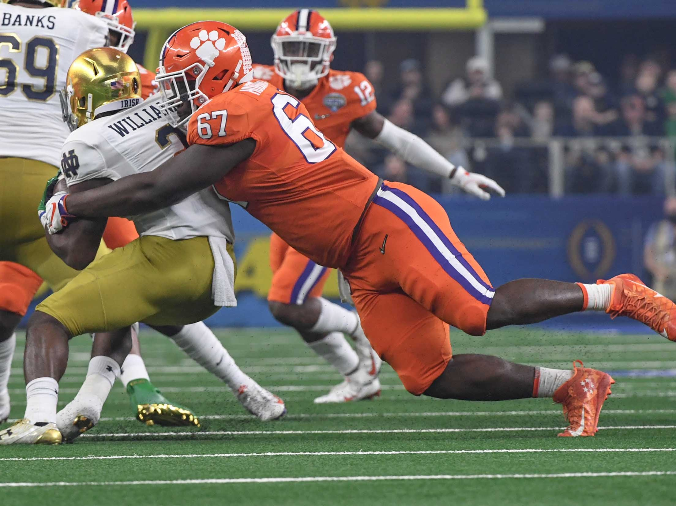 Clemson defensive lineman Albert Huggins (67) tackles Notre Dame running back Dexter Williams (2) during the first quarter of the College Football Playoff Semifinal at the Goodyear Cotton Bowl Classic at AT&T Stadium in Arlington, Texas Saturday, December 29, 2018.