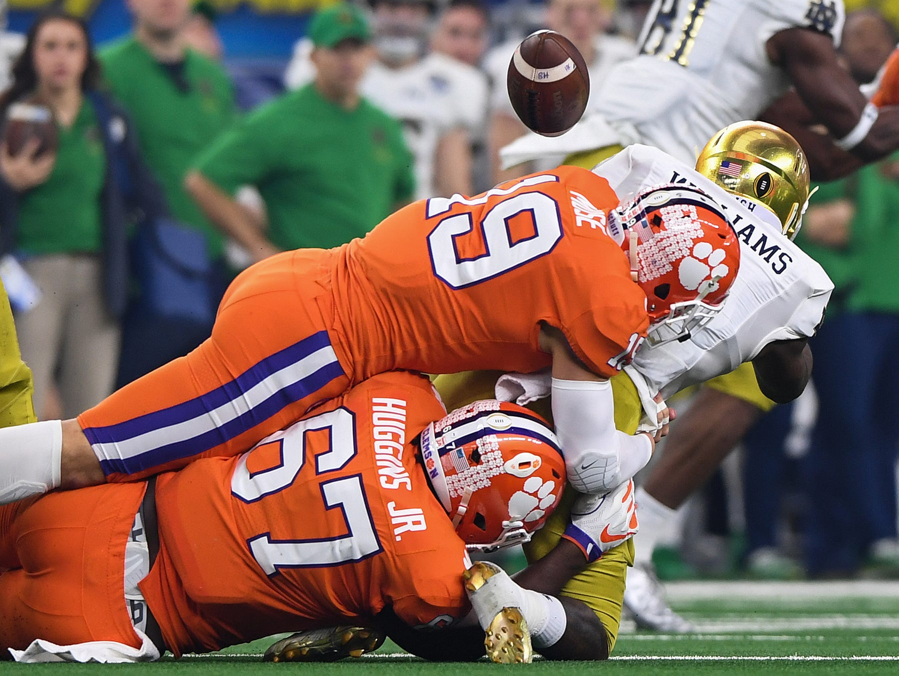 Clemson defensive back Tanner Muse (19) and defensive lineman Albert Huggins (67) bring down Notre Dame running back Dexter Williams (2) during the 1st quarter of the Goodyear Cotton Bowl at AT&T stadium in Arlington, Texas on Saturday.