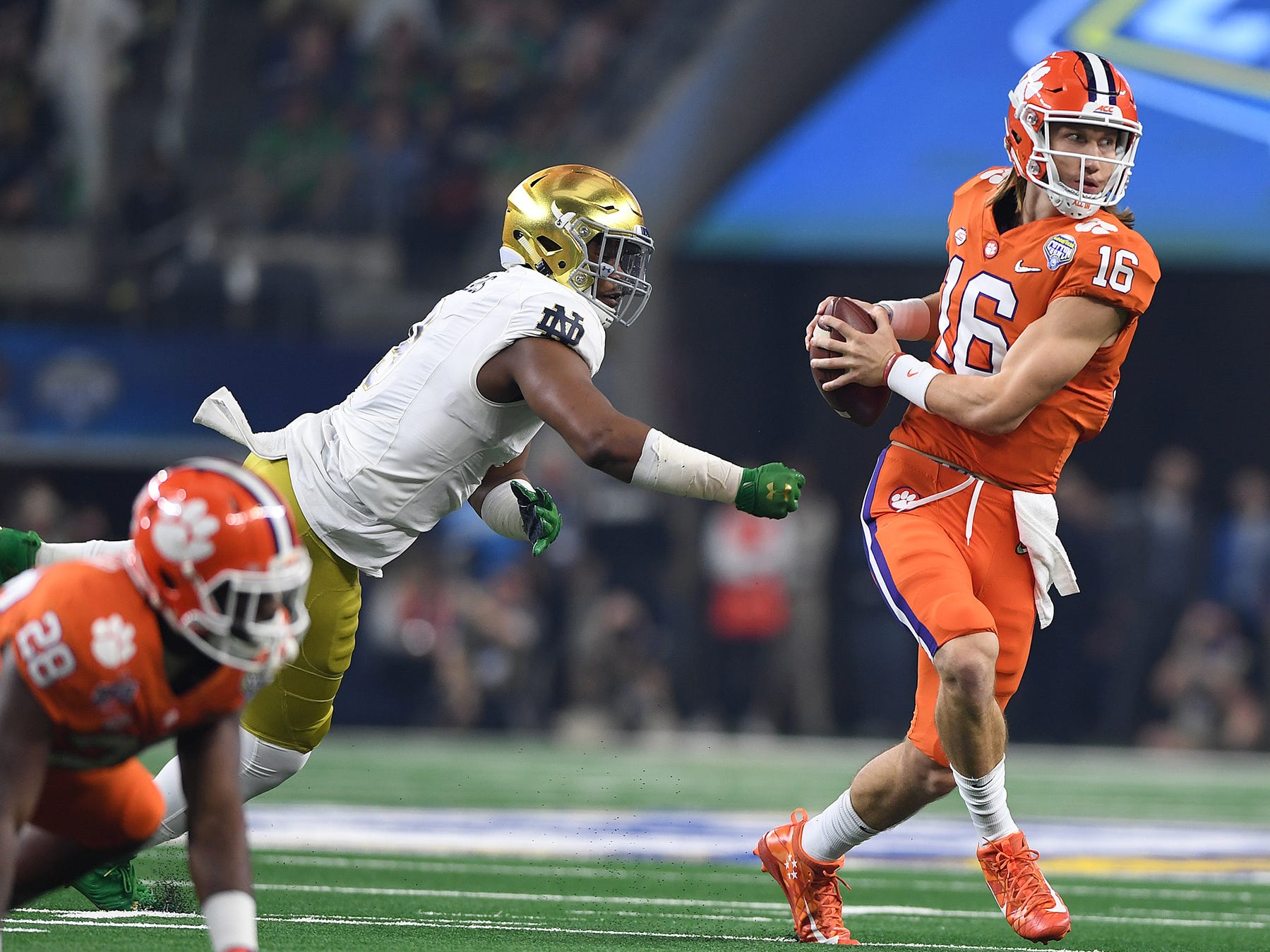 Clemson quarterback Trevor Lawrence (16) scrambles past Notre Dame defensive lineman Daelin Hayes (9) during the 1st quarter of the Goodyear Cotton Bowl at AT&T stadium in Arlington, TX Saturday, December 29, 2018.