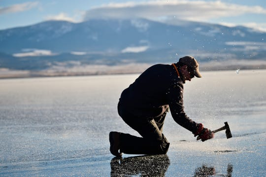 In this Tuesday, Dec. 11, 2018 photo Dale Livezey chips a hole in the ice to check its thickness at Canyon Ferry Reservoir, east of Helena, Mont. The first freeze of the year is often a hard freeze and adventurers will skate on as little as 2 inches of ice. (Thom Bridge/Independent Record via AP)