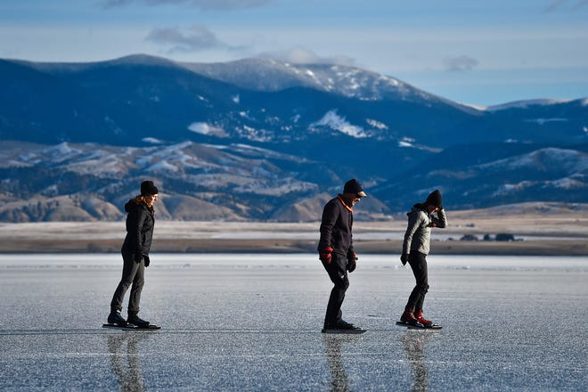 In this Tuesday, Dec. 11, 2018 photo Dale Livezey, middle, skates with Rachel and Stephanie Robey at Canyon Ferry Reservoir east of Helena, Mont. The sisters and former figure skaters from Maryland decided to enter a contest from KOA campgrounds pitching an outdoor adventure. Their proposal to come out West in search of wild ice won the grant award. (Thom Bridge/Independent Record via AP)