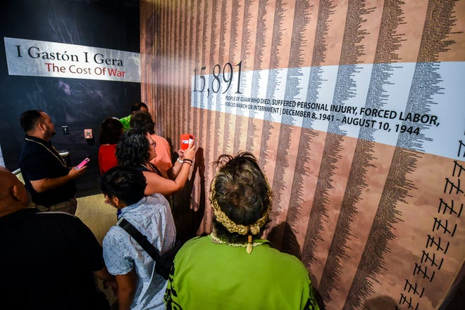 """Guests search through names of Guam residents, killed or affected during the World War II occupation of Japanese Imperial forces, as they tour the new permanent exhibit entitled, """"I Hinanao-ta Nu I Manaotao Tåno' - I CHamoru Siha"""" or """"The Journey of the CHamoru People"""" at the Sen. Antonio M. Palomo Guam Museum & Educational Facility in Hagåtña on Thursday, May 3, 2018."""