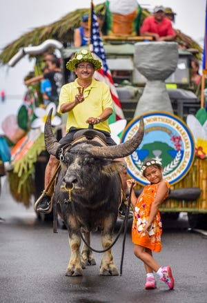 Esrae Aguon, 6, leads a carabao named Do'ak along with her passenger, Mayor of Rota Efraim Atalig, down Marine Corps Drive during the Liberation Day Parade in Hagåtna on Saturday, July 21, 2018.