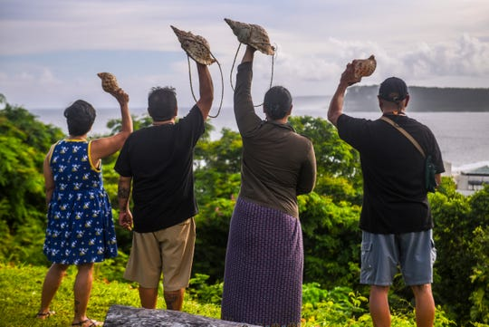 Concerned island residents raise kulus, or Chamoru shell horns, into the air as they peer out onto Tumon Bay after a peaceful solidarity event at the Sagan Kotturan Chamoru Cultural Center in Tamuning in this Aug. 9, 2018, file photo.
