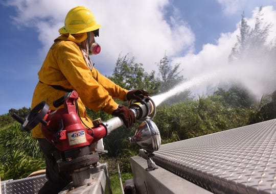 Guam Fire Department firefighter use a vehicle-mounted water cannon to saturate an area of grassland along Route 17, also known as Cross Island Road, in Santa Rita on Monday, Jan. 22, 2018. Traffic was temporarily closed on the roadway as GFD, Department of Agriculture's Forestry Division and the U.S. Navy Emergency Services firefighters battled a wildland fire that threatened homes in the area.