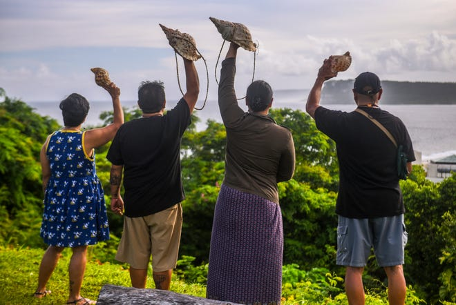 Concerned island residents raise kulus, or CHamoru shell horns, into the air as they peer out onto Tumon Bay after a peaceful solidarity event at the Sagan Kotturan Chamoru Cultural Center in Tamuning in this Aug. 9, 2018 file photo. Opponents of military training in the Commonwealth of the Northern Mariana Islands recently lost their appeal in federal court.