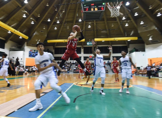 St. John's player Michael Min (0) adjusts his shot in mid-air against St. Paul Warriors defenders during their Independent Interscholastic Athletic Association of Guam Boys' Basketball Championship game at the University of Guam Calvo Field House on March 9, 2018.