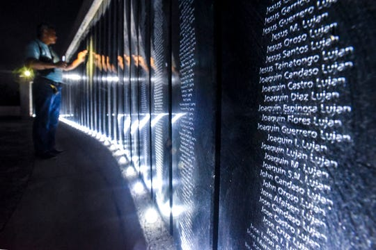 Rick Torres searches for names of family members engraved upon the Memorial Wall of Names at the War in the Pacific National Historical Park's Asan Bay Overlook on Nimitz Hill on Friday, Dec. 7, 2018. Several war survivors, along with their descendents attending the event, shared stories of experiences impacted upon them during the Japanese military occupation of Guam, from December 1941 through July 1944, and the recapturing of the island by American armed forces.