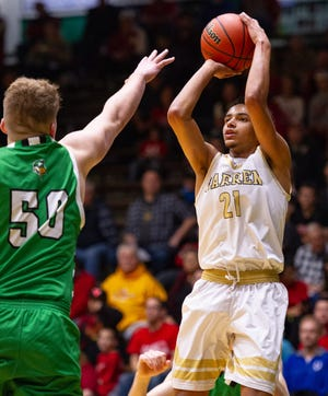 Warren Central High School senior Jamisen Smith (21) puts up a shot over the defense of Valparaiso High School sophomore Cooper Jones (50) during the first half of action. New Castle High School hosted the annual Hall of Fame Classic tournament, Saturday, Dec. 29, 2018.