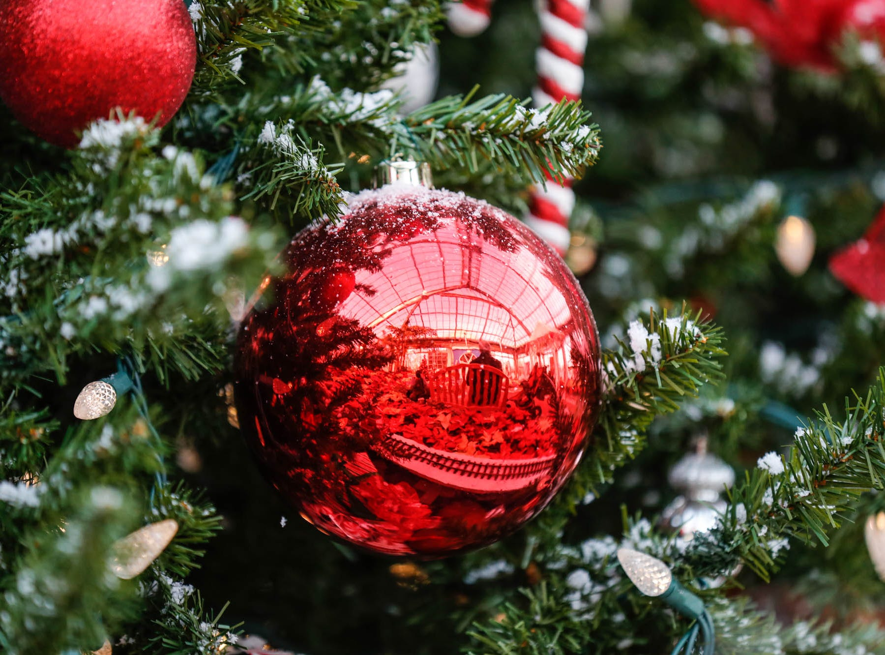 A Christmas ornament reflects in the Conservatory Crossing holiday display at the Garfield Park Conservatory on Saturday, Dec. 29, 2018.