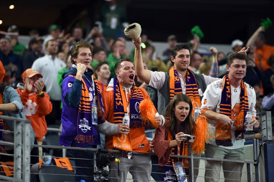 Clemson fans cheer on their team during warm ups before of the NCAA Cotton Bowl semi-final playoff football game.