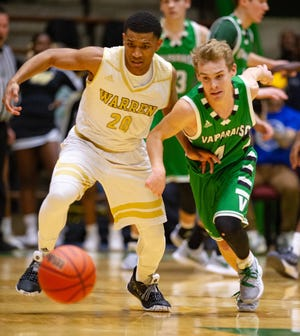 Warren Central High School senior Isiah Moore (20) and Valparaiso High School senior Colin Walls (4) battle for the ball during the first half of action. New Castle High School hosted the annual Hall of Fame Classic tournament, Saturday, Dec. 29, 2018.