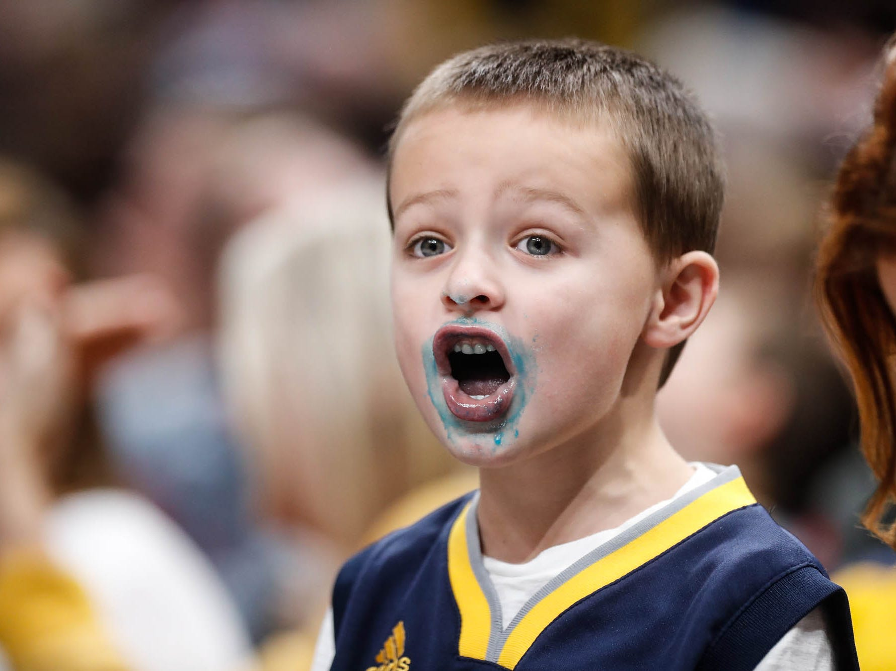 Fan Mason Ward cheers on the Pacers while eating cotton candy during a game between the Indiana Pacers and the Detroit Pistons at at Bankers Life Fieldhouse in Indianapolis on Friday, Dec. 28, 2018.