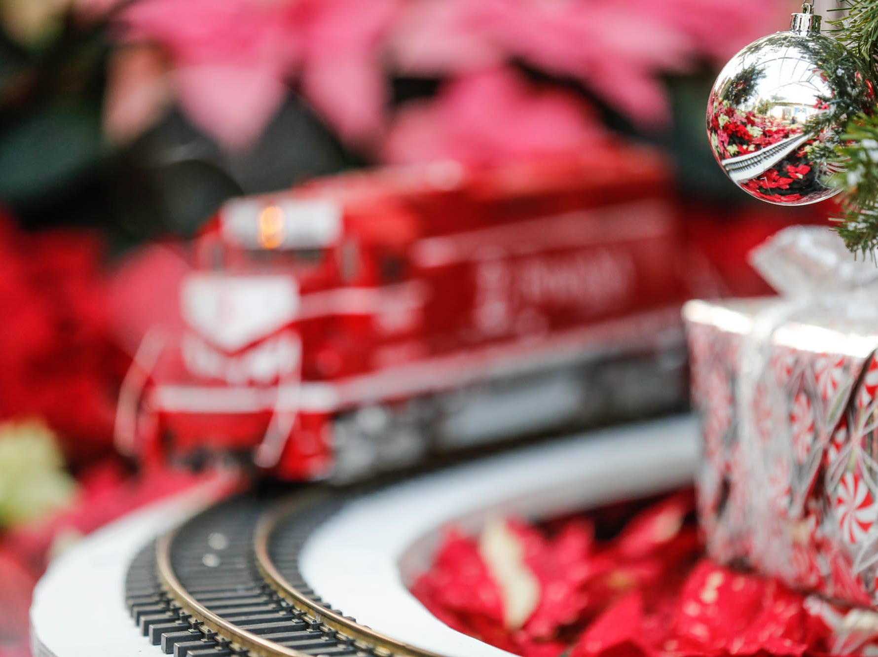 A Christmas ornament reflects the train tracks in the Conservatory Crossing holiday display at the Garfield Park Conservatory on Saturday, Dec. 29, 2018.