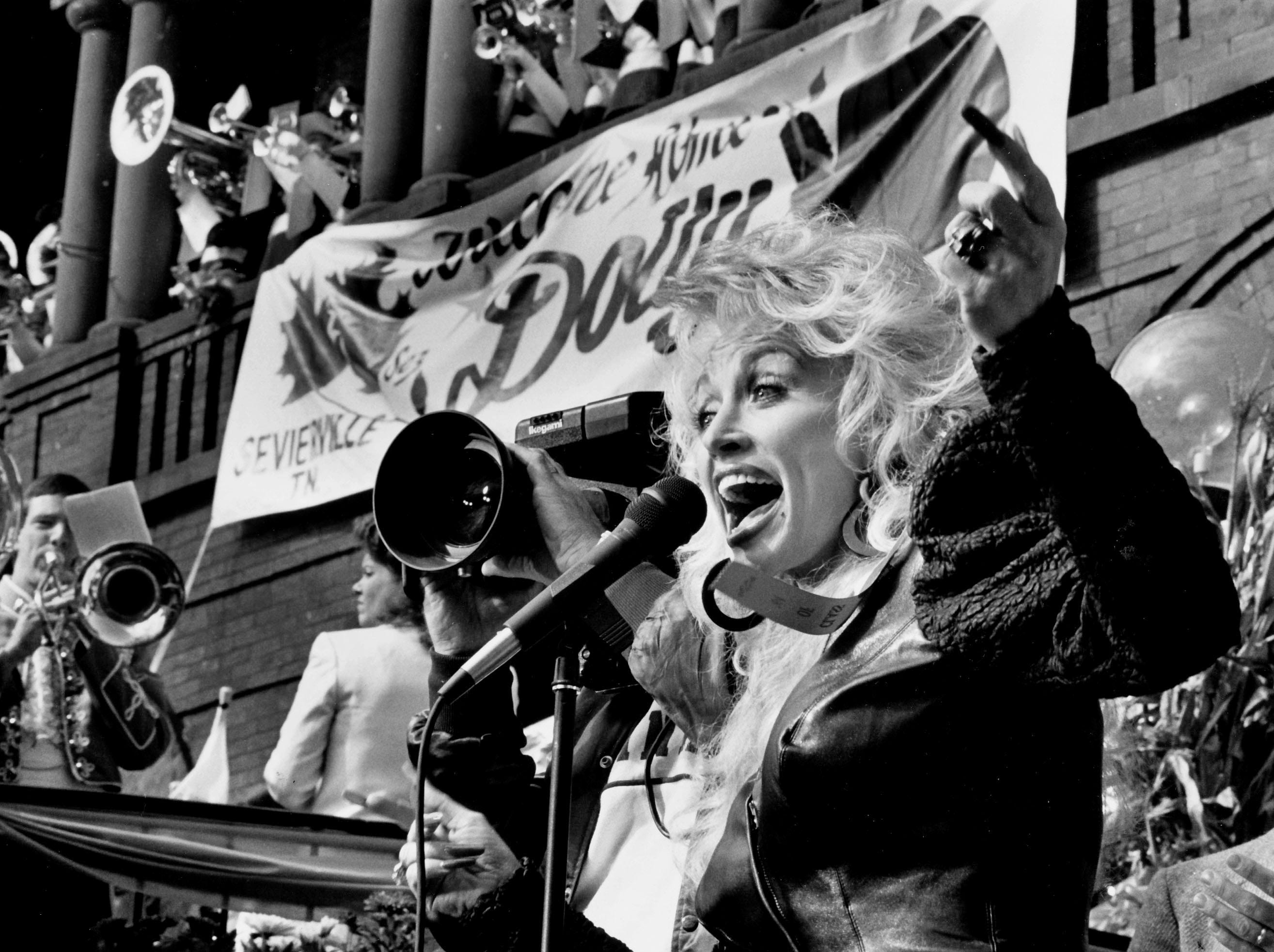 Dolly Parton cheers the crowd during a TV shoot on October 7, 1987 outside the Sevierville Courthouse.