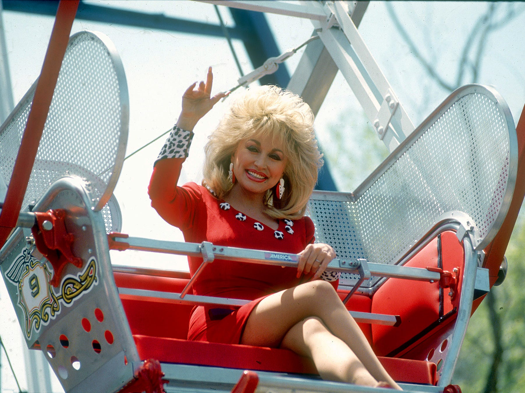 Waving from her seat on the over 100-year-old ferris wheel at Dollywood, Dolly Parton marks the park's seasonal opening in April 23, 1993.
