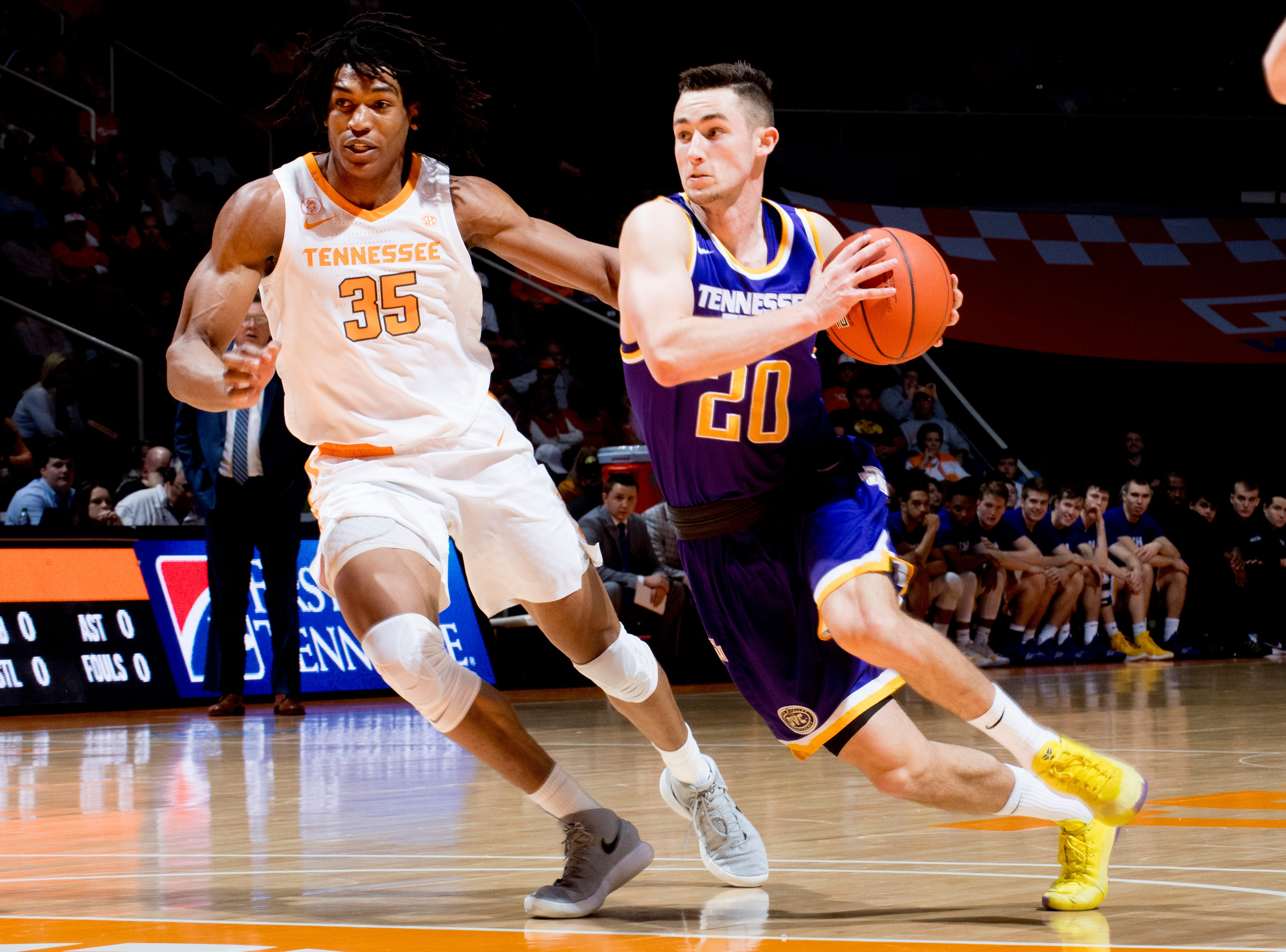 Tennessee Tech guard Hunter Vick (20) drives the ball past Tennessee guard/forward Yves Pons (35) during a game between Tennessee and Tennessee Tech at Thompson-Boling Arena in Knoxville, Tennessee on Saturday, December 29, 2018.