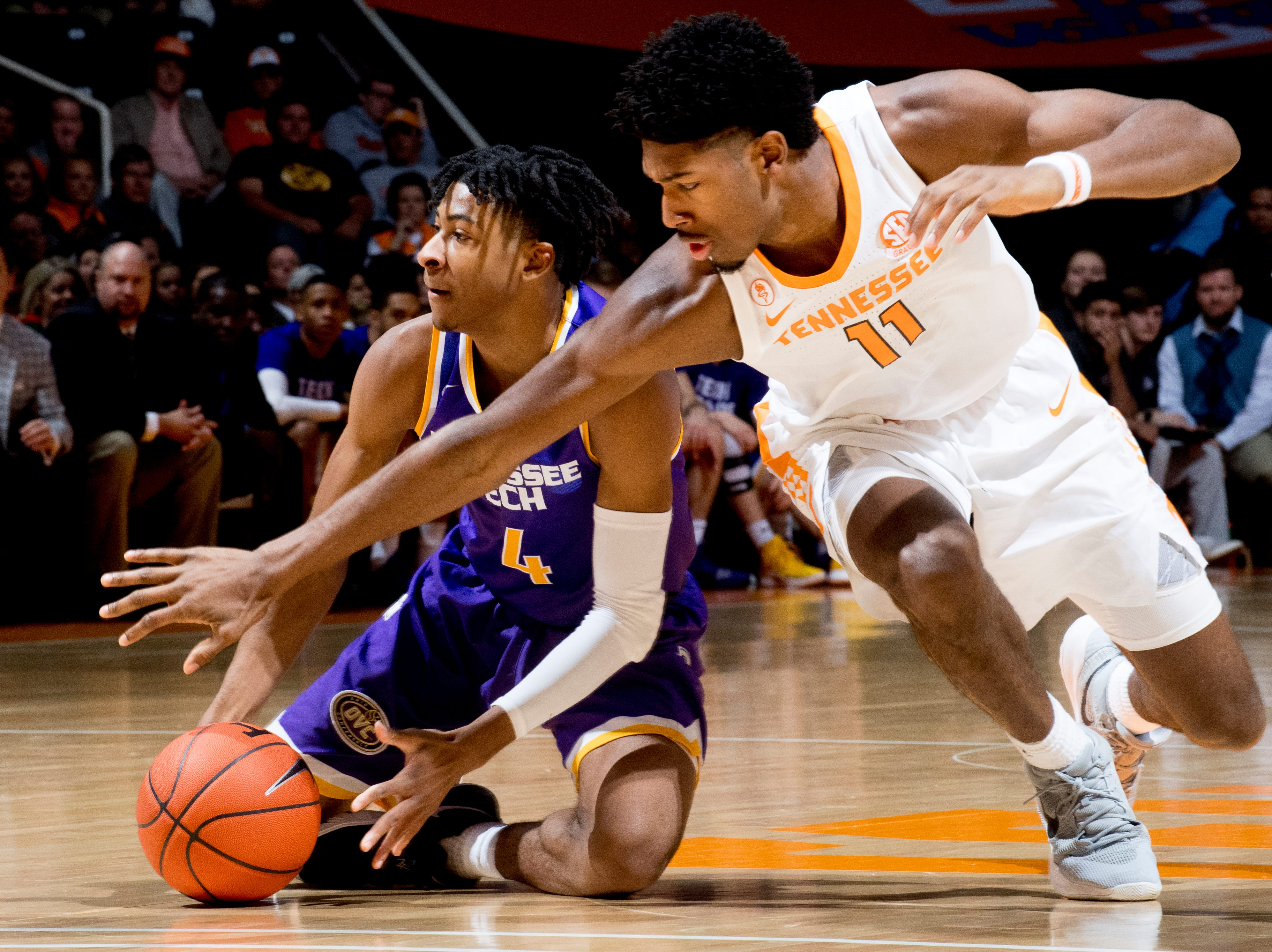 Tennessee Tech guard Jr. Clay (4) and Tennessee forward Kyle Alexander (11) chase a loose ball during a game between Tennessee and Tennessee Tech at Thompson-Boling Arena in Knoxville, Tennessee on Saturday, December 29, 2018.