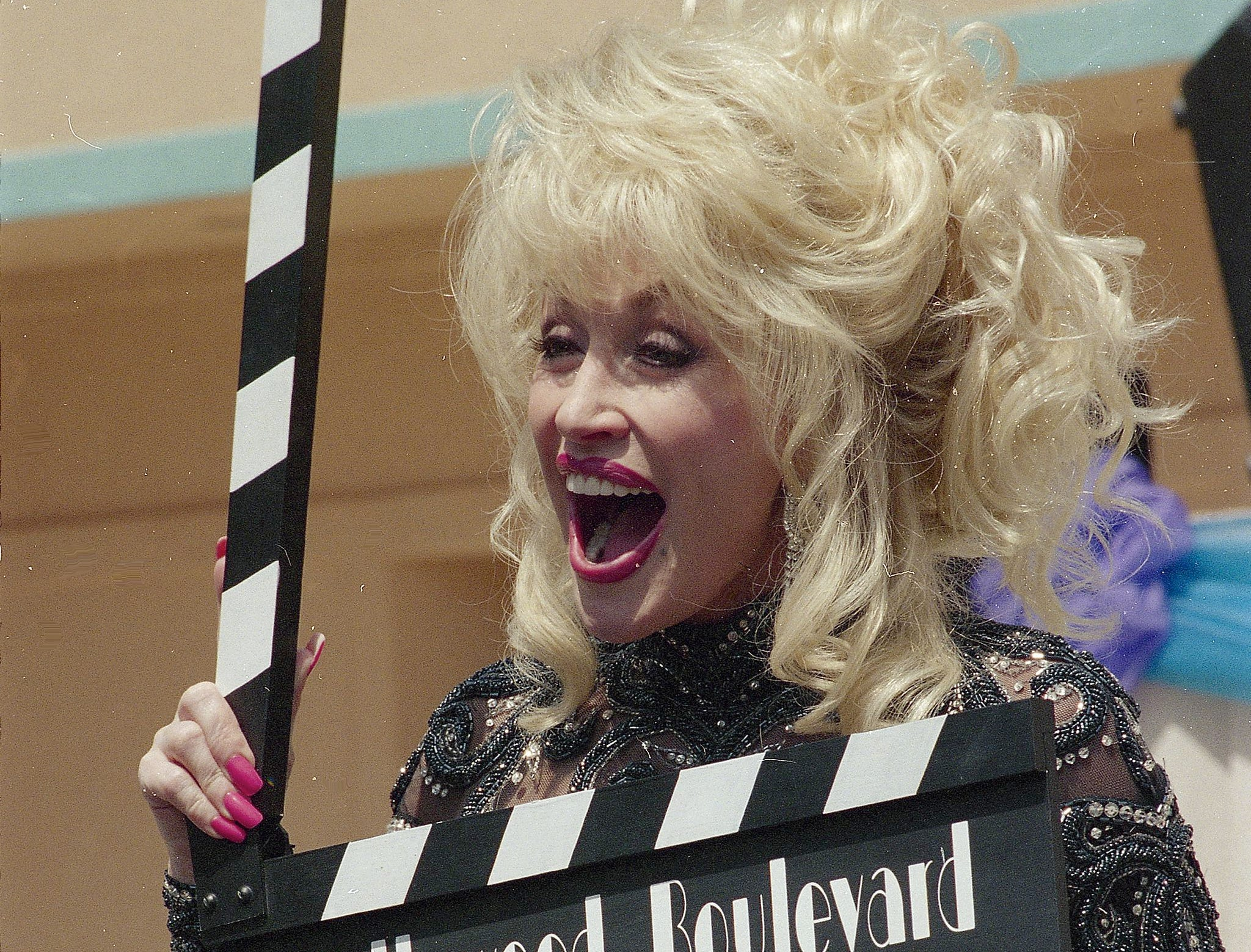 "Using a movie ""slate"" marker, Dolly Parton marks the seasonal opening of her theme park, Dollywood on April 20, 1996."