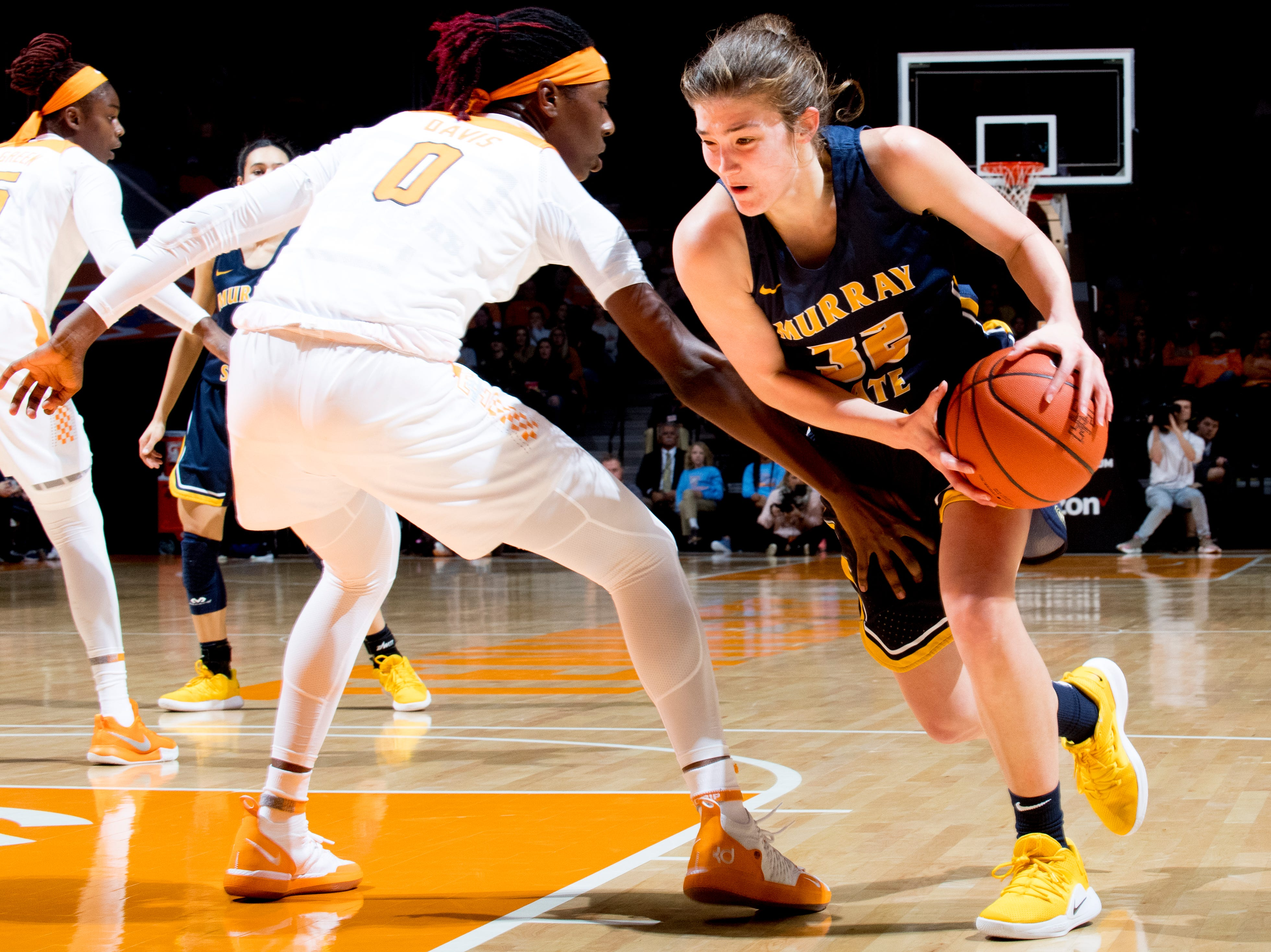Murray State forward/guard Alexis Burpo (32) dribbles past Tennessee guard/forward Rennia Davis (0) during a game between the Tennessee Lady Vols and Murray State at Thompson-Boling Arena in Knoxville, Tennessee on Friday, December 28, 2018.