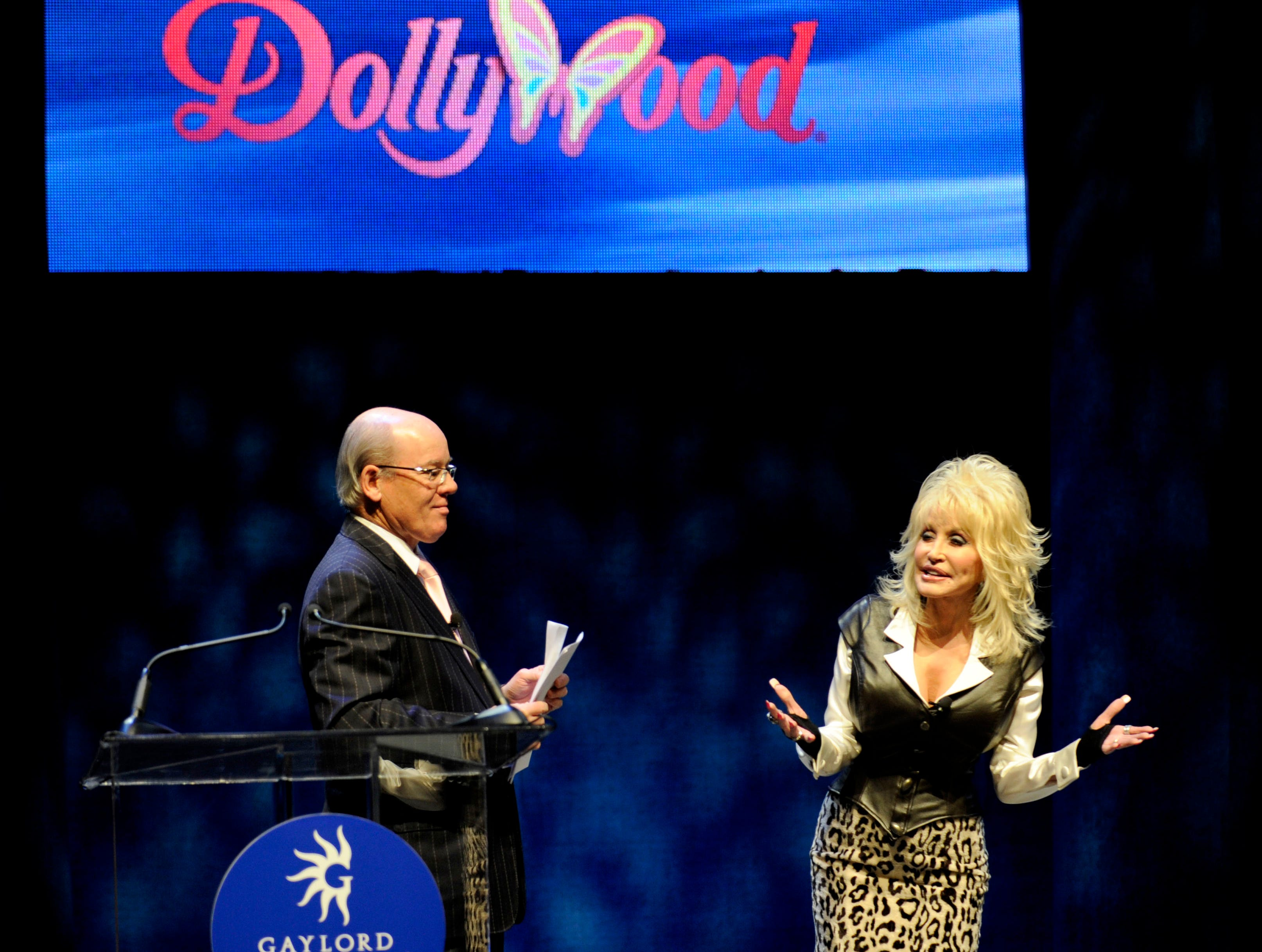 Dolly Parton stands on stage with Gaylord Entertainment CEO Colin Reed as they announced Thursday, Jan. 19, 2012 a new water and snow park to be built near the Opryland Hotel in Nashville.