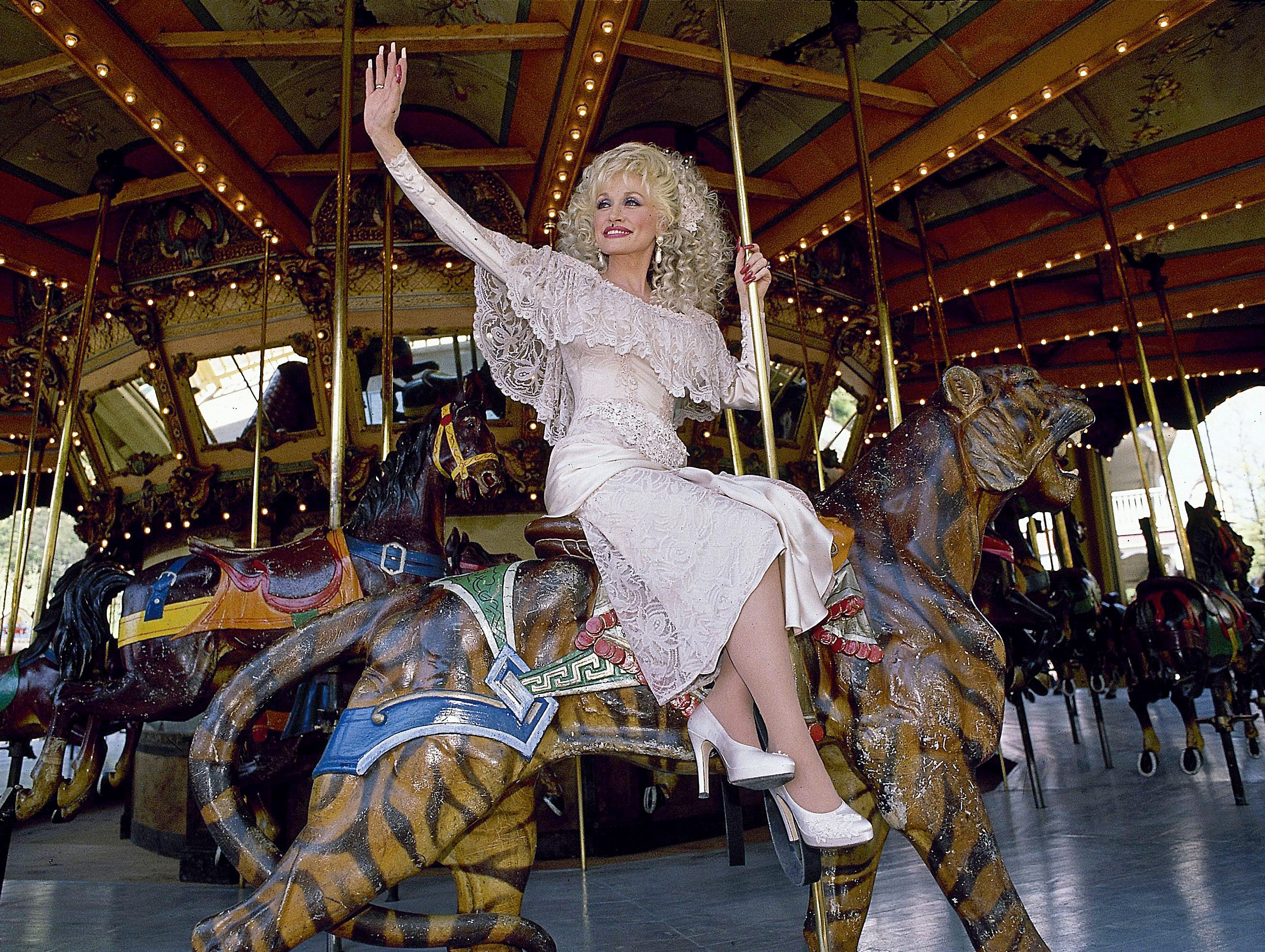Dolly Parton opens Dollywood for a new season April 27, 1990 with a ride on the carousel.