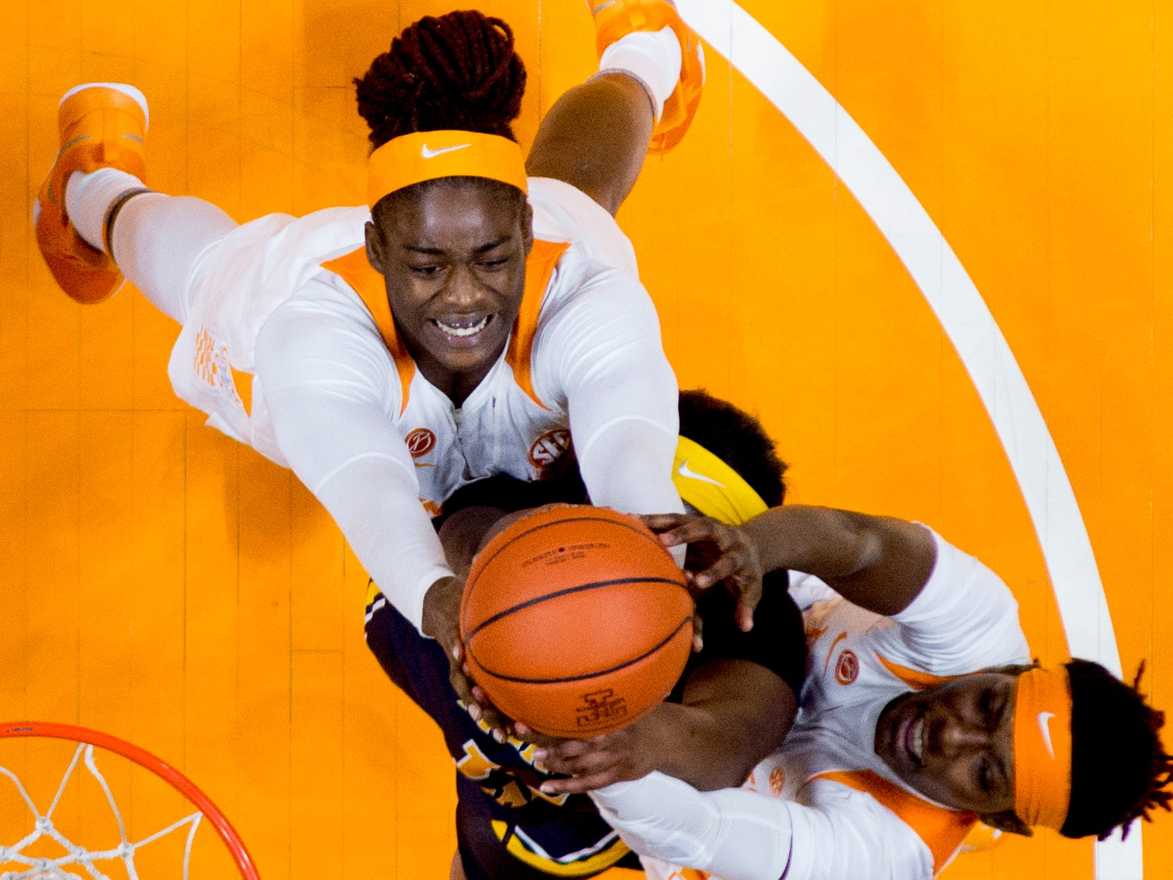 Tennessee forward Cheridene Green (15) and Tennessee guard/forward Rennia Davis (0) attempt to grab the ball from Murray State forward Evelyn Adebayo (14) during a game between the Tennessee Lady Vols and Murray State at Thompson-Boling Arena in Knoxville, Tennessee on Friday, December 28, 2018.