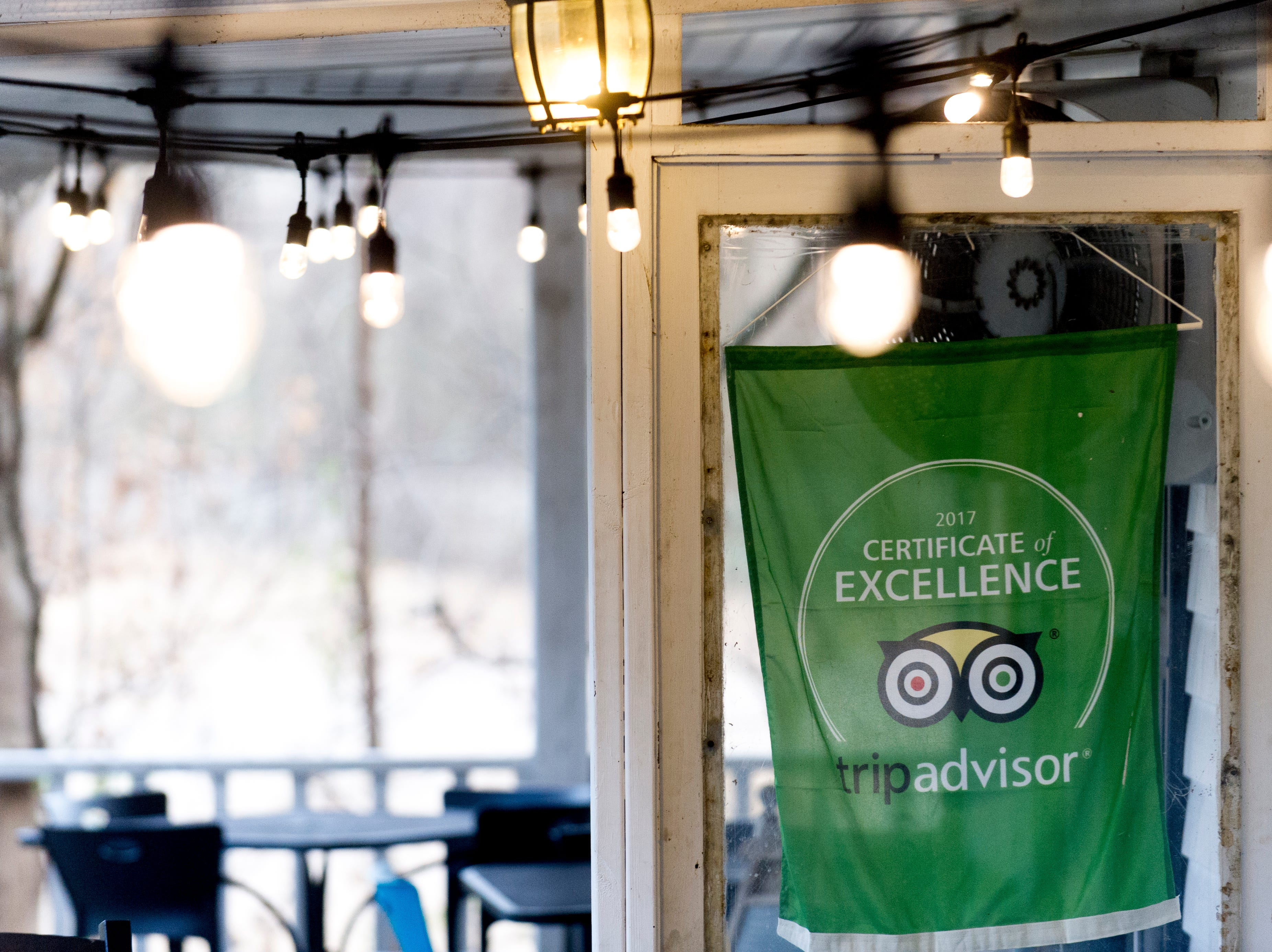 A banner advertising the restaurants' Certificate of Excellence on Trip Advisor hangs on the porch at The Front Porch Restaurant in Powell, Tennessee on Saturday, December 29, 2018. For five years, owner Bart Elkins has worked to revive that experience of the front porch being used as the focus for family and friends.