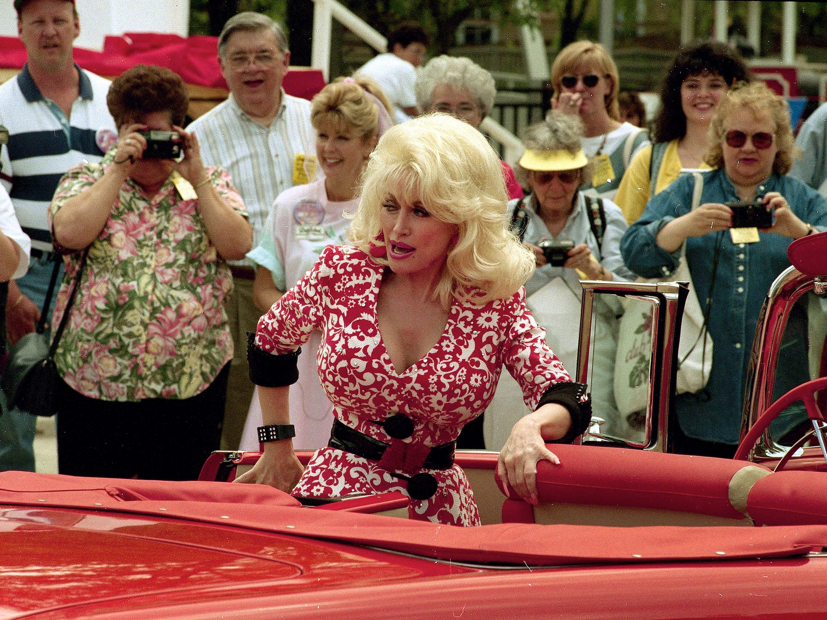 Dolly Parton climbs into a 1955 Chevrolet convertible at the season opening of Dollywood on April 21, 1995.