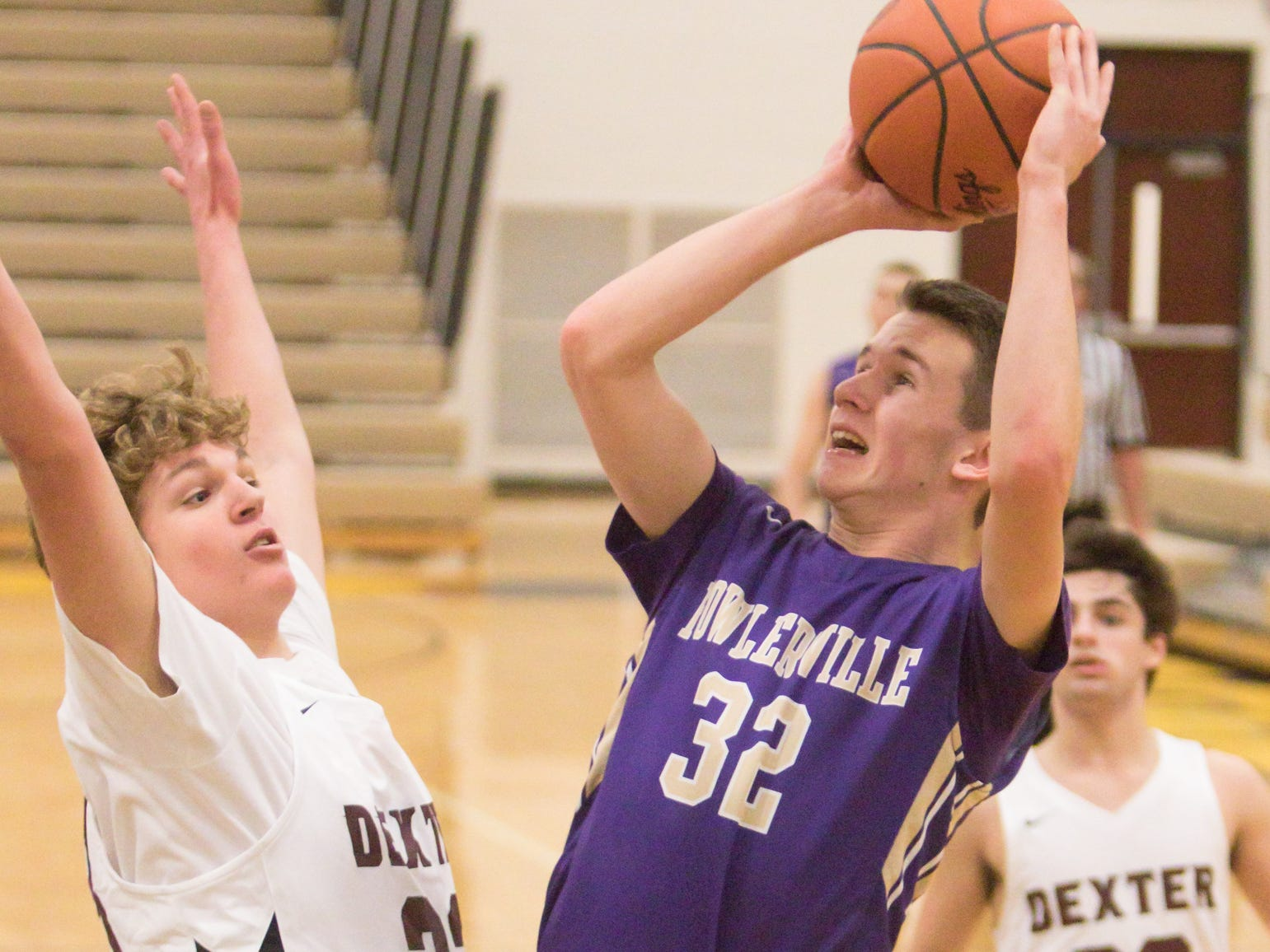 Fowlerville's Wes Latson shoots and connects, guarded by Dexter's Kellen Porter in the fourth quarter of the tournament game at Hartland Friday, Dec. 28, 2018.