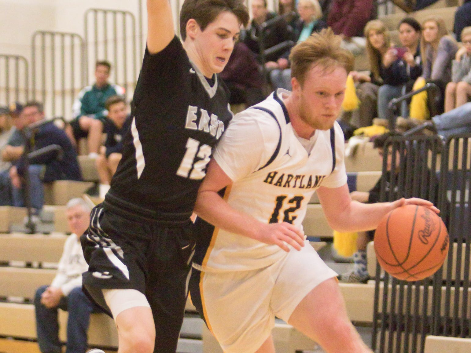 Hartland's Evan Metz dribbles past South Lyon East's Bryce Bird in the tournament game Friday, Dec. 28, 2018.