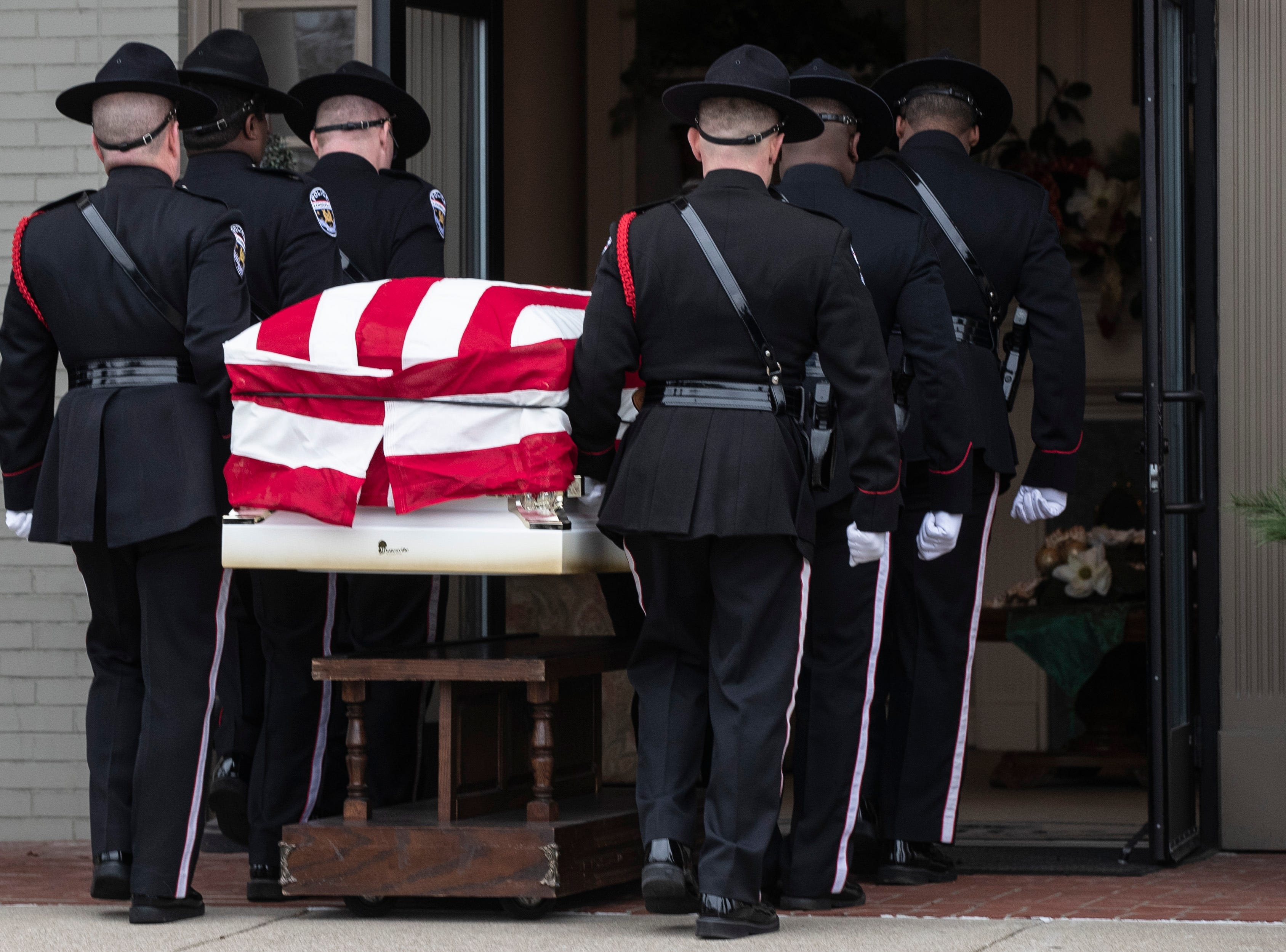 Police officers carry Deidre Mengedoht's coffin into the Resthaven Funeral Home on Bardstown Road in Louisville, Ky. December 29, 2018