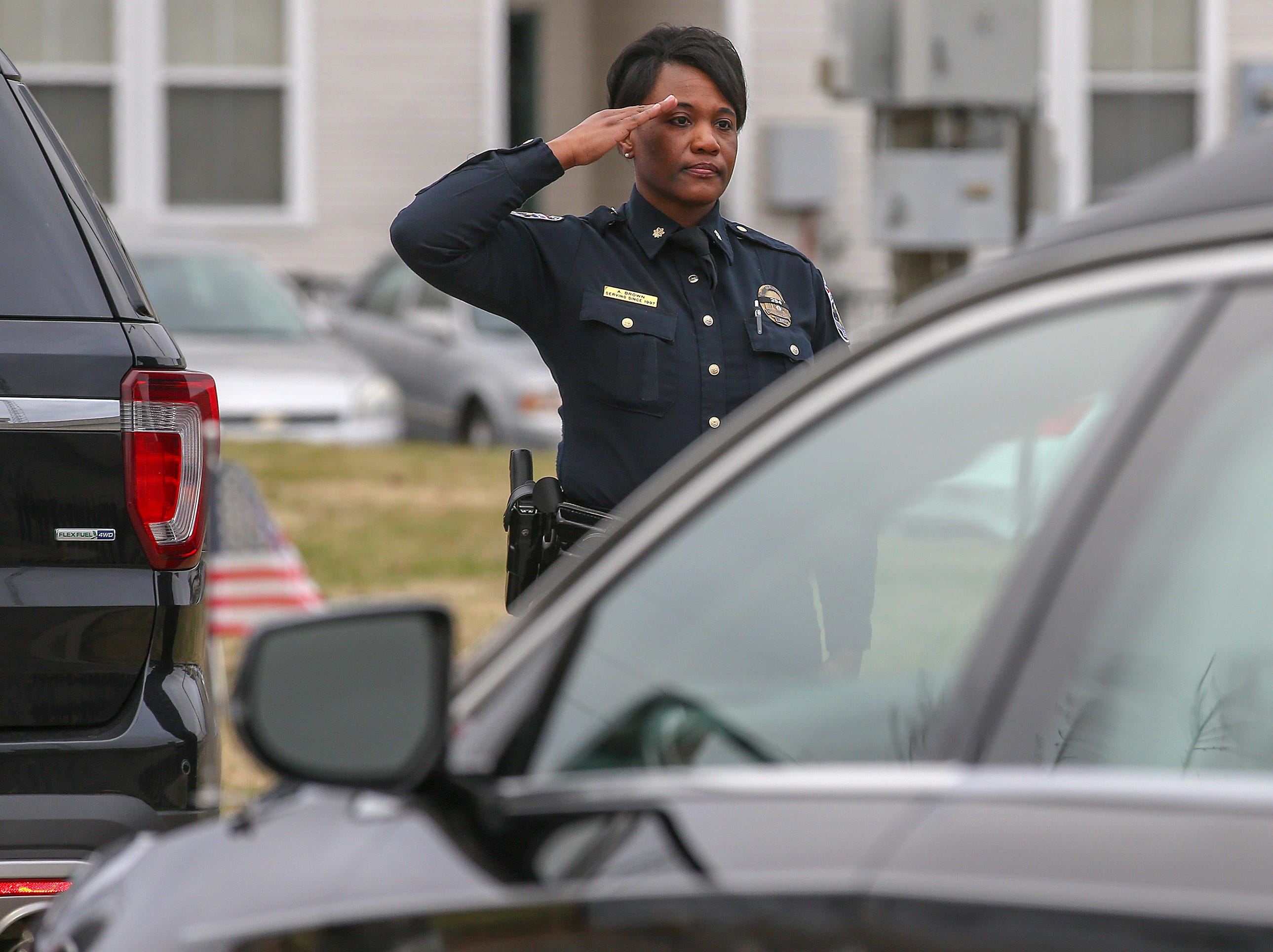 Police officers salute the hearse carrying Deidre Mengedoht as it stops at the LMPD 2nd Division headquarters in Park DuValle. December 29, 2018