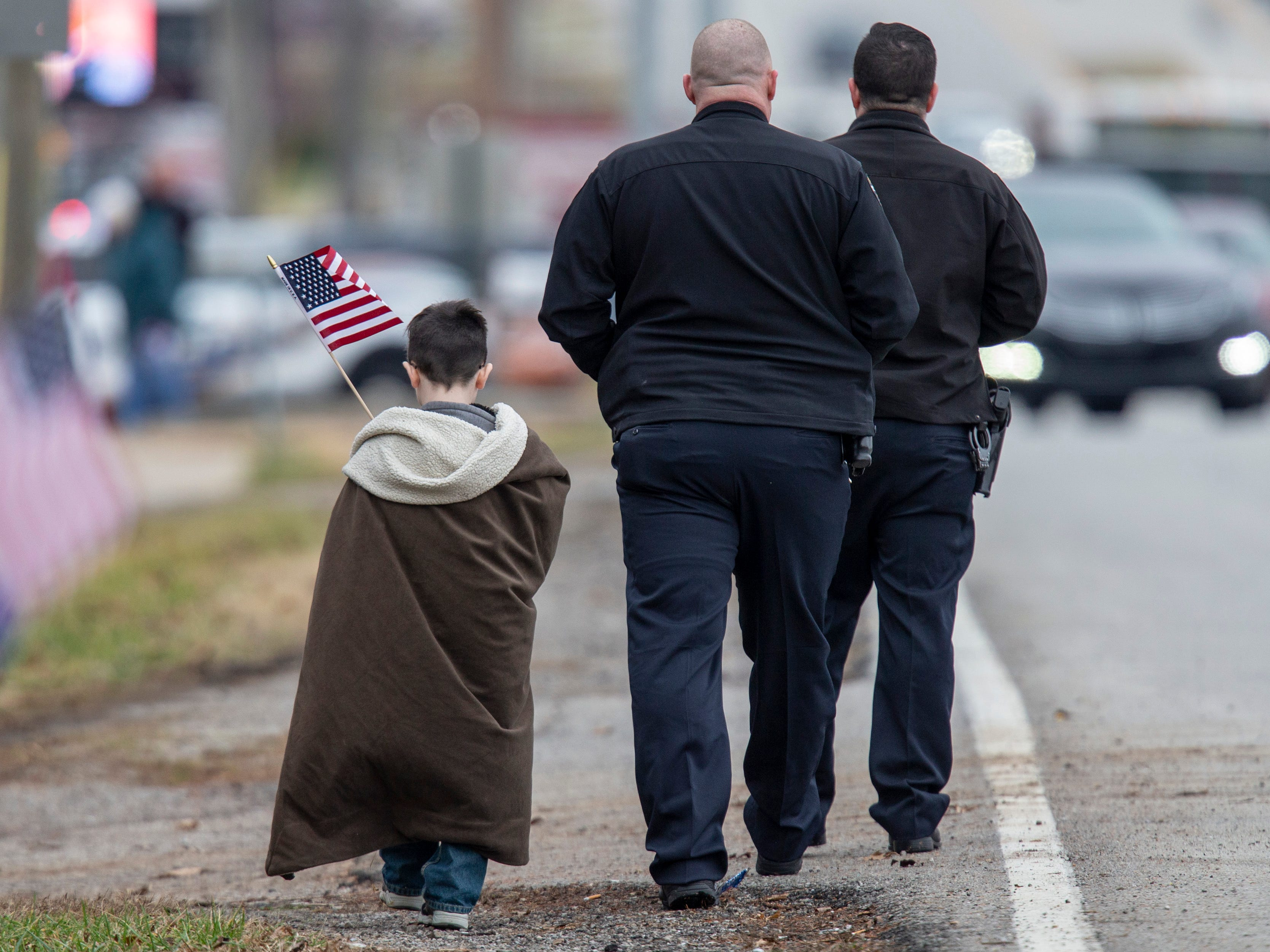 A young boy carries an American flag as he walks with two police officers following the procession for Det. Deidre Mengedoht on Saturday in Louisville, Ky.