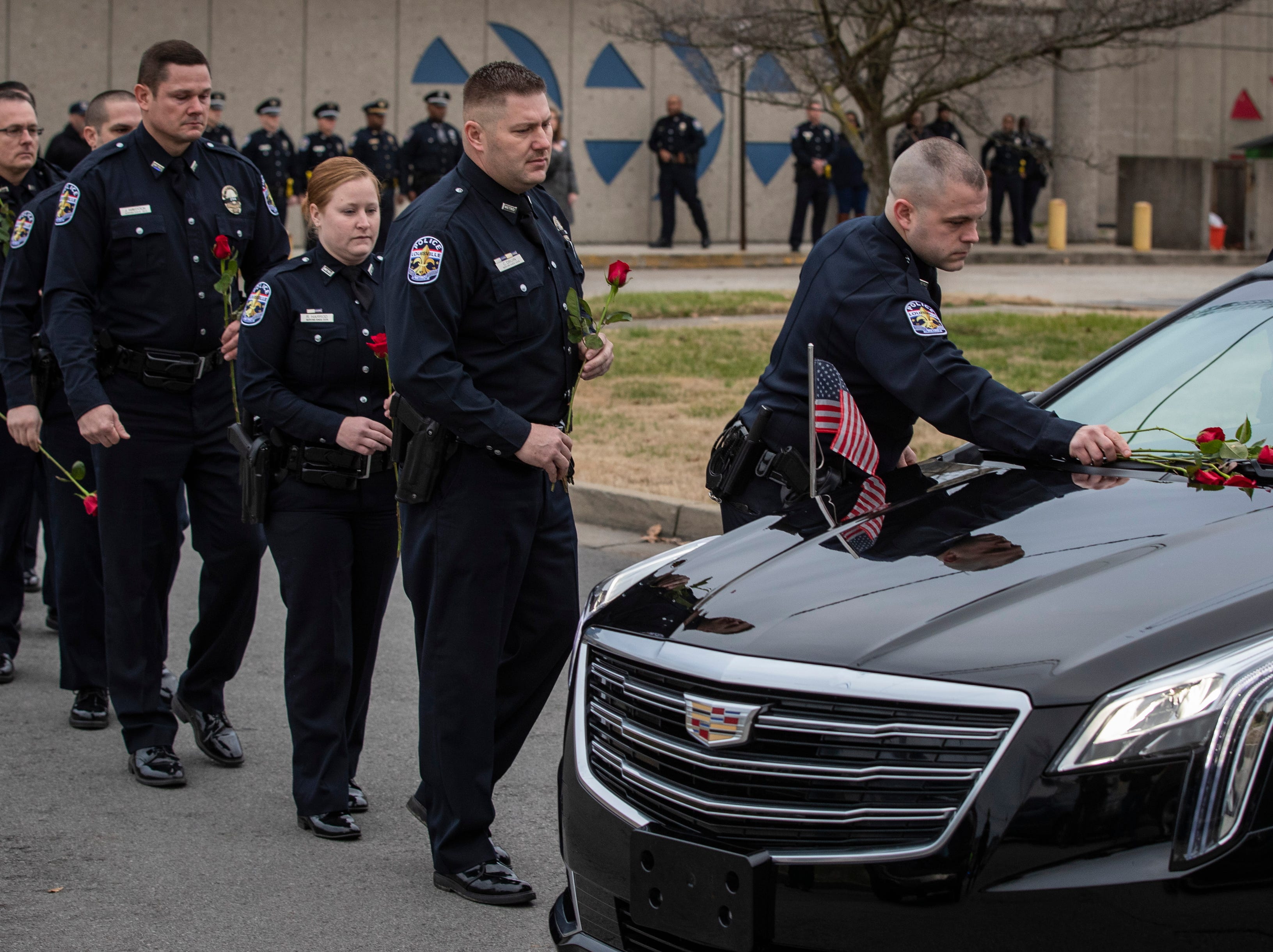 Police officers lay roses onto the hearse carrying Deidre Mengedoht as it stops at the LMPD 2nd Division headquarters in Park DuValle in Louisville, Ky. December 29, 2018
