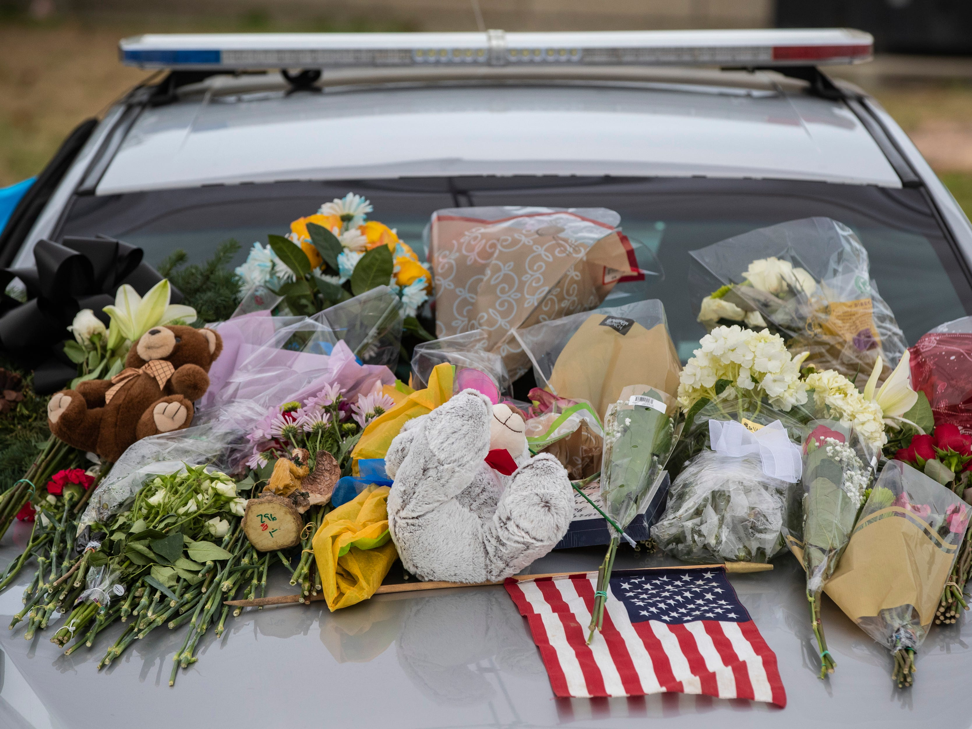 Flowers and flags lie on the hood of a remembrance patrol car for Deidre Mengedoht at the LMPD 2nd Division headquarters in Park DuValle. December 29, 2018