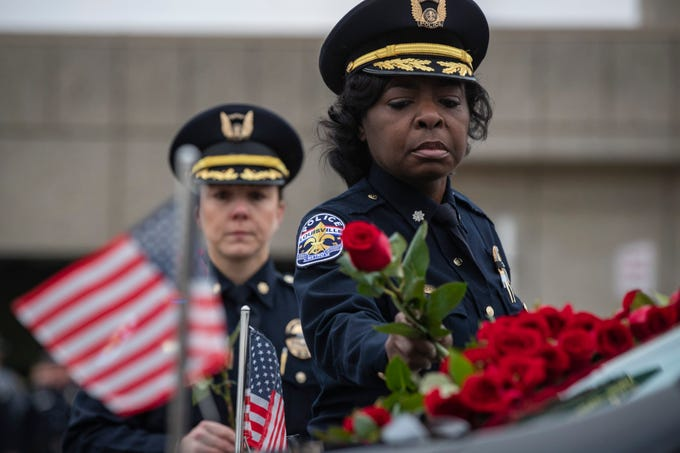LMPD assistant chief of police, LaVita Chavous lays a rose onto the hearse carrying Deidre Mengedoht as it stops at the LMPD 2nd Division headquarters in Park DuValle in Louisville, Ky. December 29, 2018