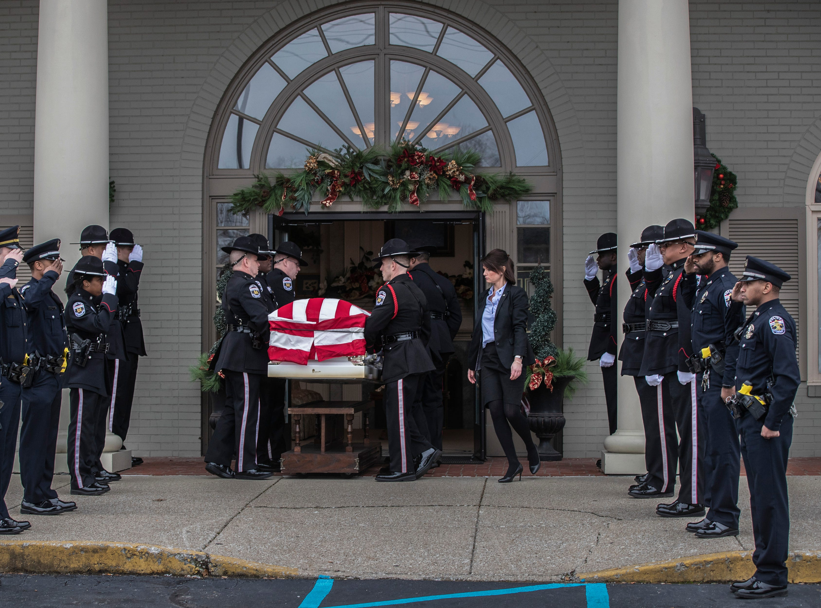 Det. Deidre Mengedoht's casket is carried into Resthaven Funeral Home following the procession Saturday through Louisville, Ky. December 29, 2018